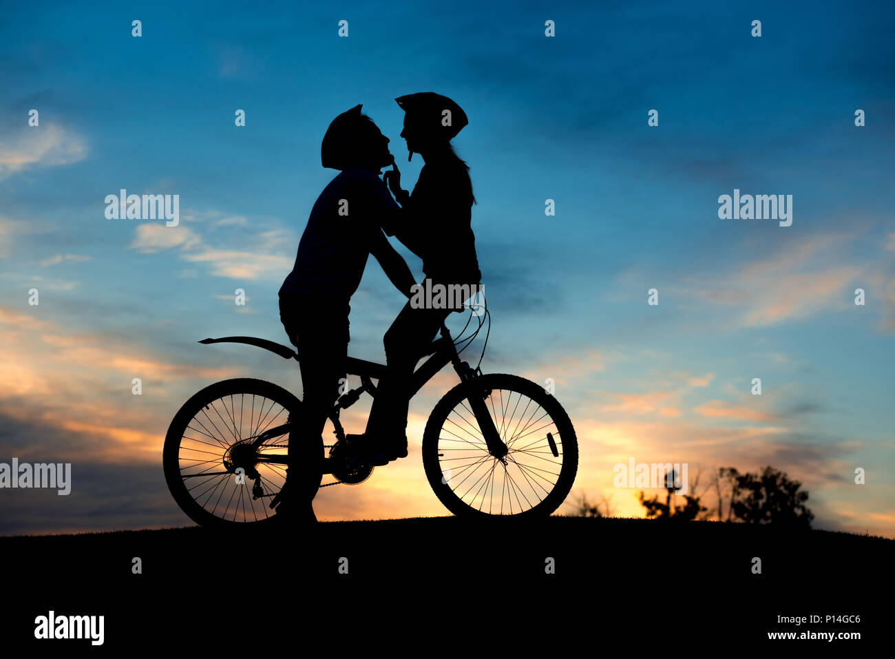 Couple kissing on the top of hill at sunset. Silhouette of bicyclists is kissing on summer nature background with beautiful clouds in the sky. Romanti - Stock Image