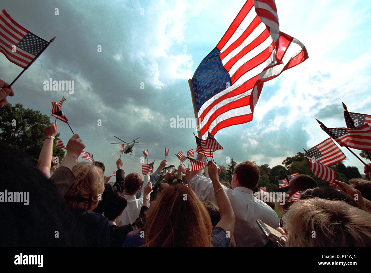 Staff members wave American flags as they gather on the South Lawn of the White House Friday, Sept. 21, 2001, as President George W. Bush and Mrs. Laura Bush depart for Camp David aboard Marine One. Stock Photo