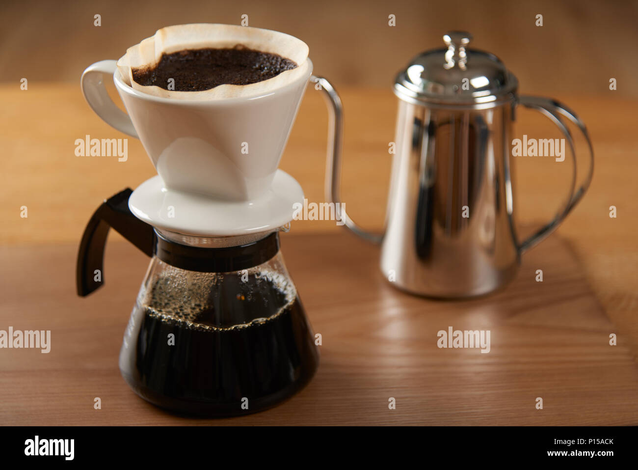 ceramic hand drip coffee brewer (dripper) and drip ground coffee on a glass server with stainless drip pot - Stock Image