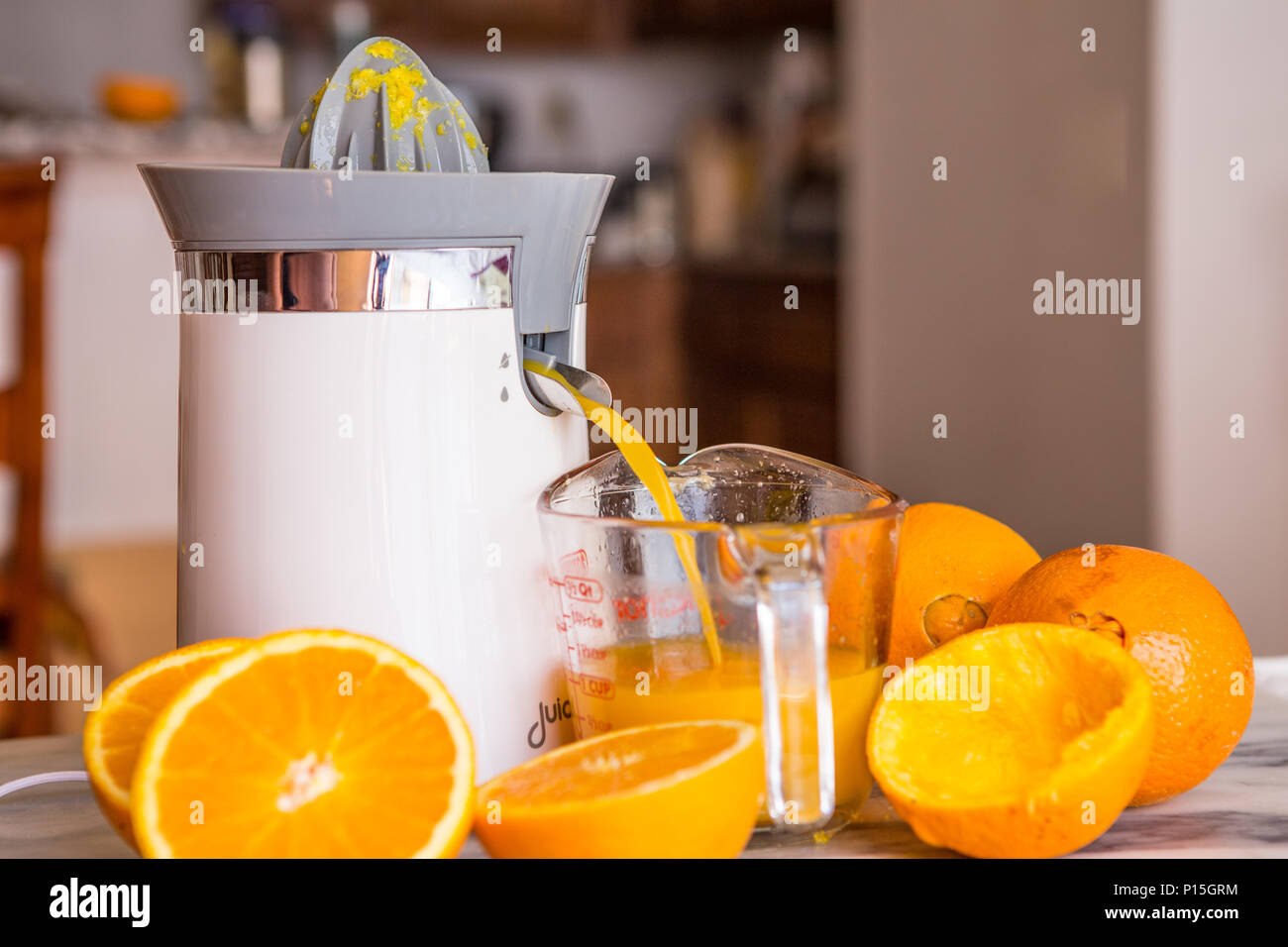 tabletop electric orange and citrus fruit juicer in a home kitchen with fresh whole and cut oranges . Stock Photo