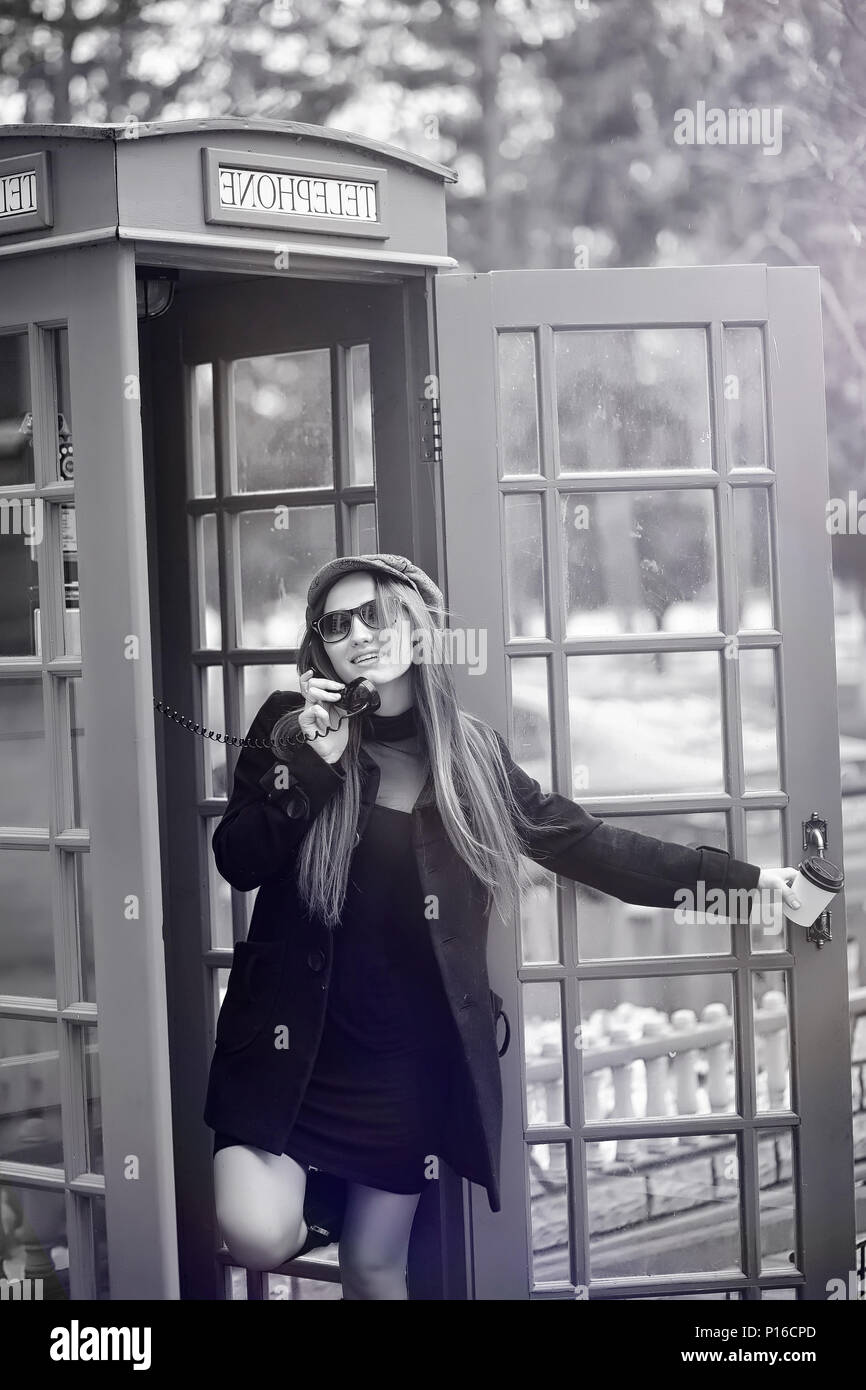 Beautiful young girl in a phone booth. The girl is talking on the phone from the payphone. English telephone booth in the street and a woman talking o - Stock Image