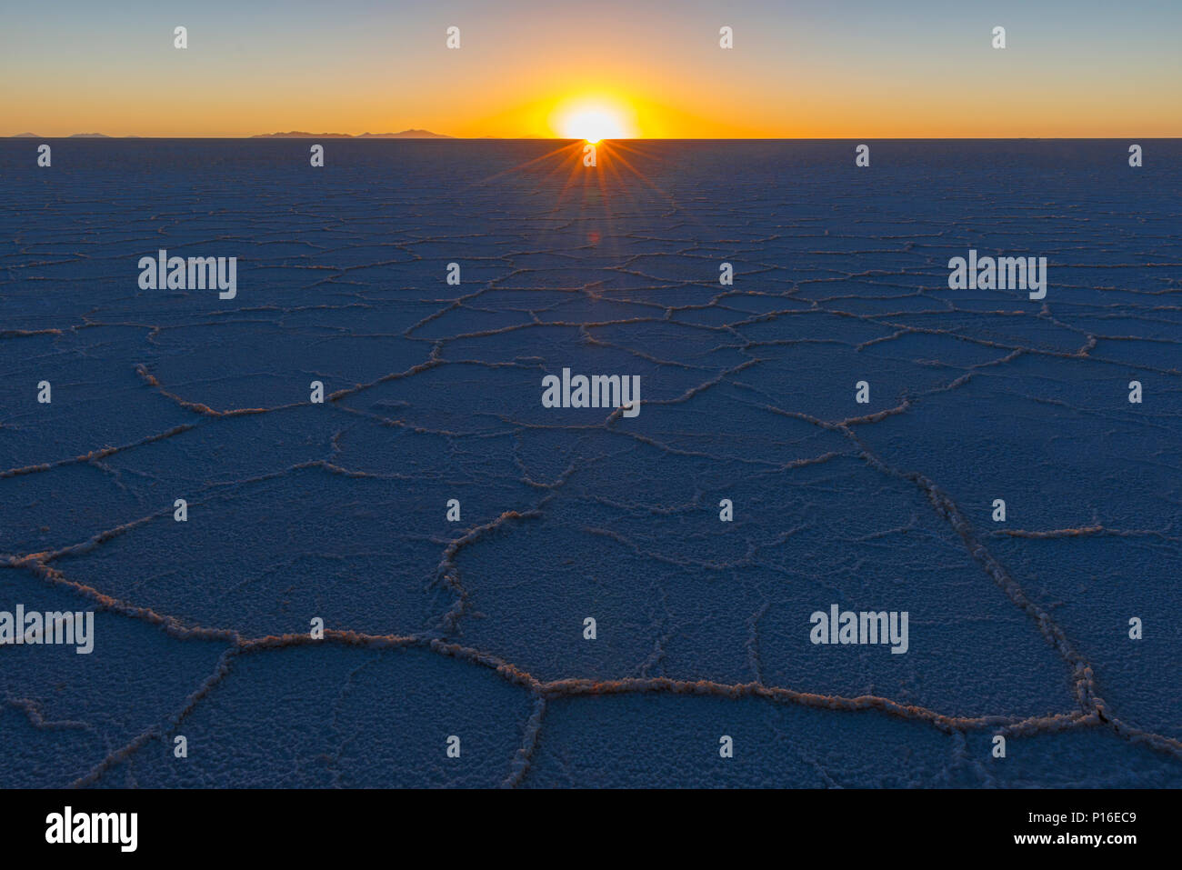 The last sun rays shining on the desert of salt in the Uyuni salt flat at sunset in the Bolivian altiplano (Salar de Uyuni), Bolivia, South America. - Stock Image