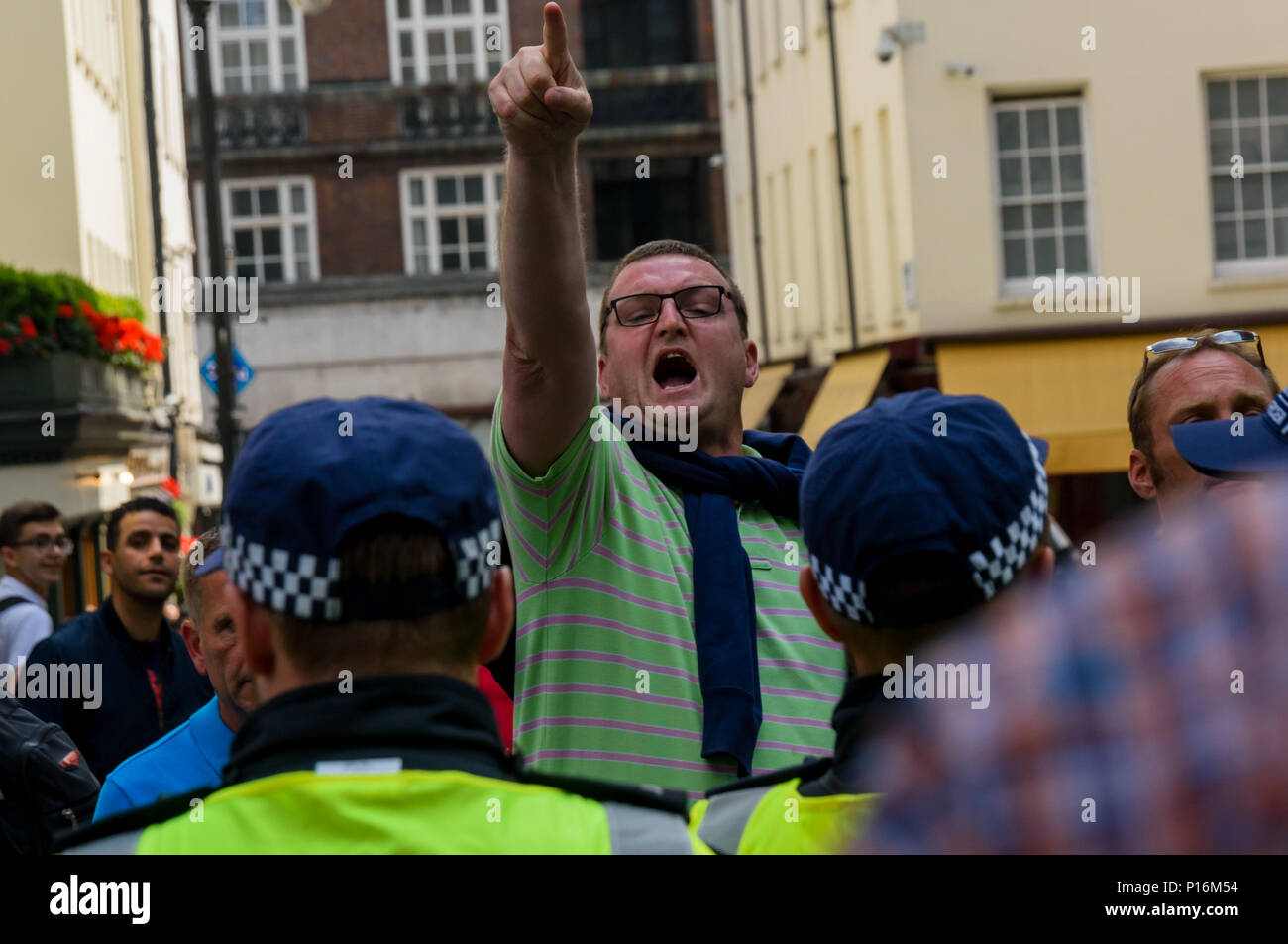 June 10, 2018 - London, UK. 10th June 2018. Police quickly led away a group of right-wing men who had come to disrupt the event as a large crowd squashed into the street in front of the Saudi Arabian embassy for a rally in support of the oppressed people of Palestine and others around the world. This man shouts insults and points at the protesters and press as police lead him away. The event, organised by the Justice for Palestine Committee, is supported by the Islamic Human Rights Commission and a wide range of pro-Palestinian organisations, and was opposed by the Zionist Federation and some  - Stock Image