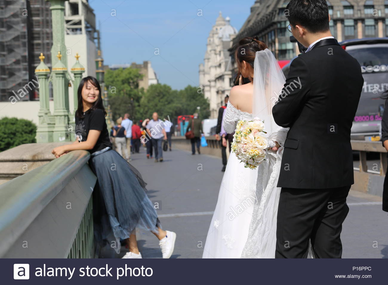 London, UK. 11th June 2018. There was glorious weather in London this morning as early grey skies cleared and brought sunshine to the banks of the Thames. Ideal weather for any one getting married as are Hai and Miao who came to Westminster Bridge with a friend to take wedding photographs. Credit: Clearpix/Alamy Live News Stock Photo