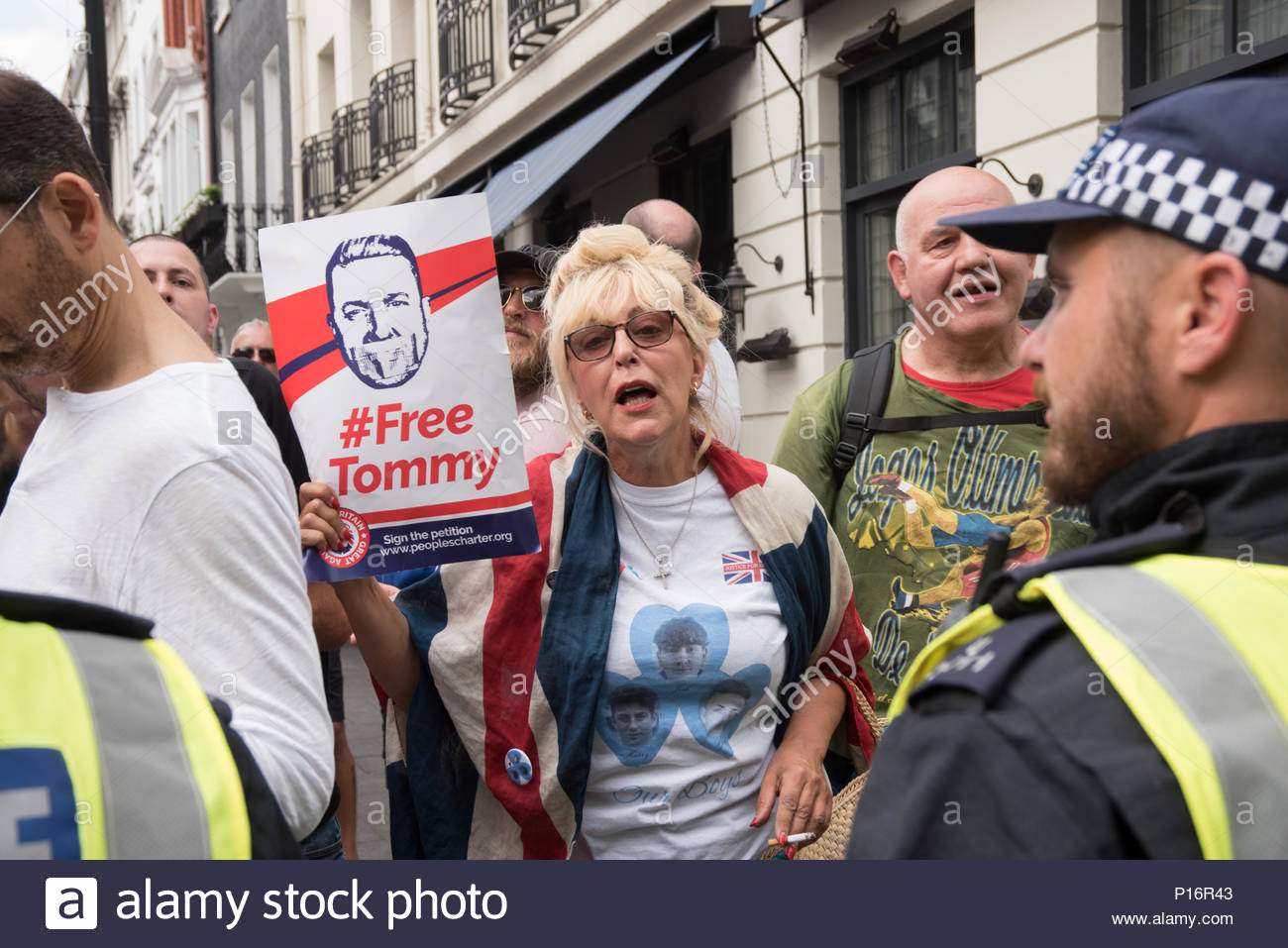 London United Kingdom 10 June 2018 A supporter of former leader of the anti-immigrant EDL Tommy Robinson holds a sign reading 'Tommy Robinson' as Pro-Palestinian demonstrators rally outside of the Saudi Arabian Embassy in London for Al Quds Day on June 10, 2018. The annual Al-Quds march is held around the world during the last week of Ramadan and was initiated in 1979 to express support for the Palestinians and oppose Zionism and Israel. (c) copyright CrowdSpark/See LI - Stock Image