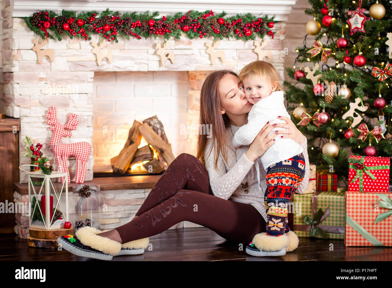 Young mother sitting with little daughter near decorated fireplace and christmas tree. - Stock Image