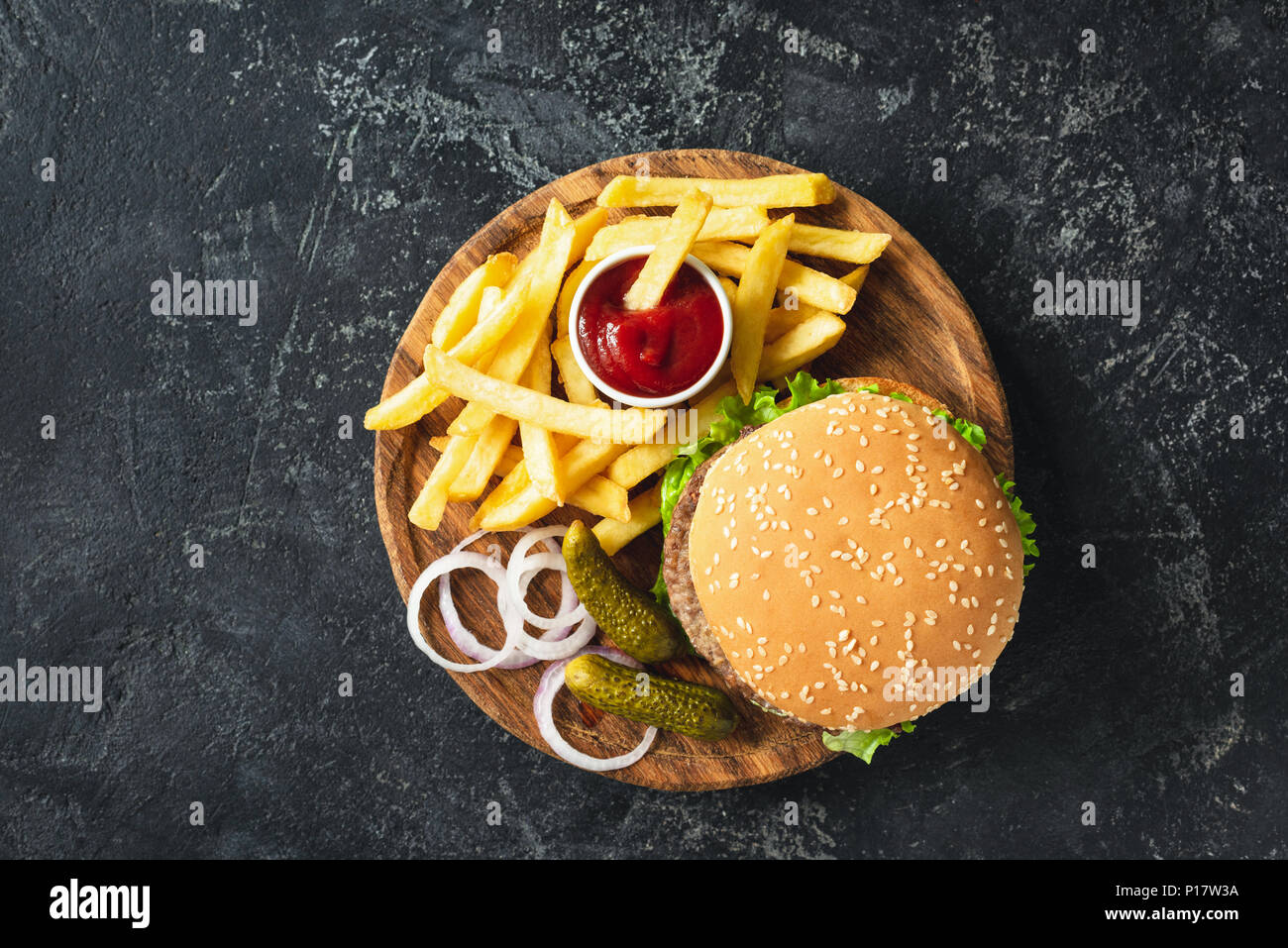Burger, hamburger or cheeseburger served with french fries, pickles and onion on wooden board. Top view. Fast food concept Stock Photo