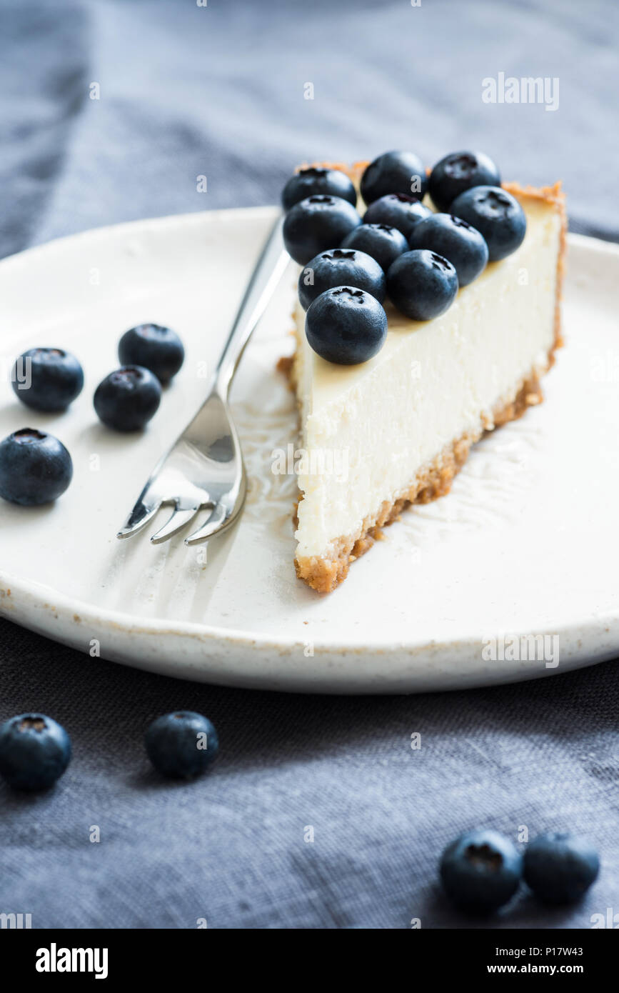 Slice of classical new york cheesecake topped with fresh blueberries. Closeup view, selective focus - Stock Image