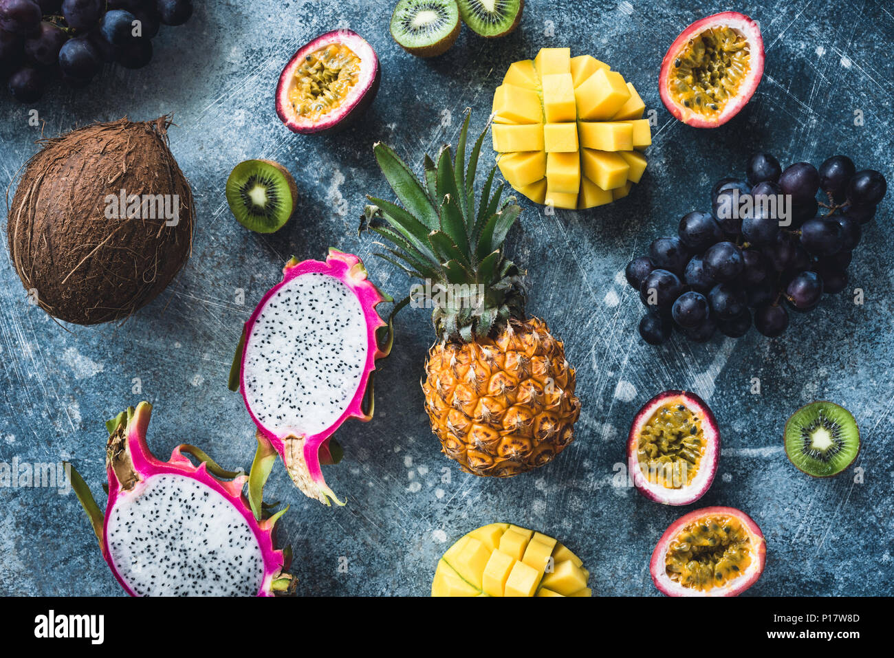 Tropical fruits on stone background, flat lay, table top view. Pitaya, passion fruit, grapes, kiwi, coconut, mango and pineapple - Stock Image