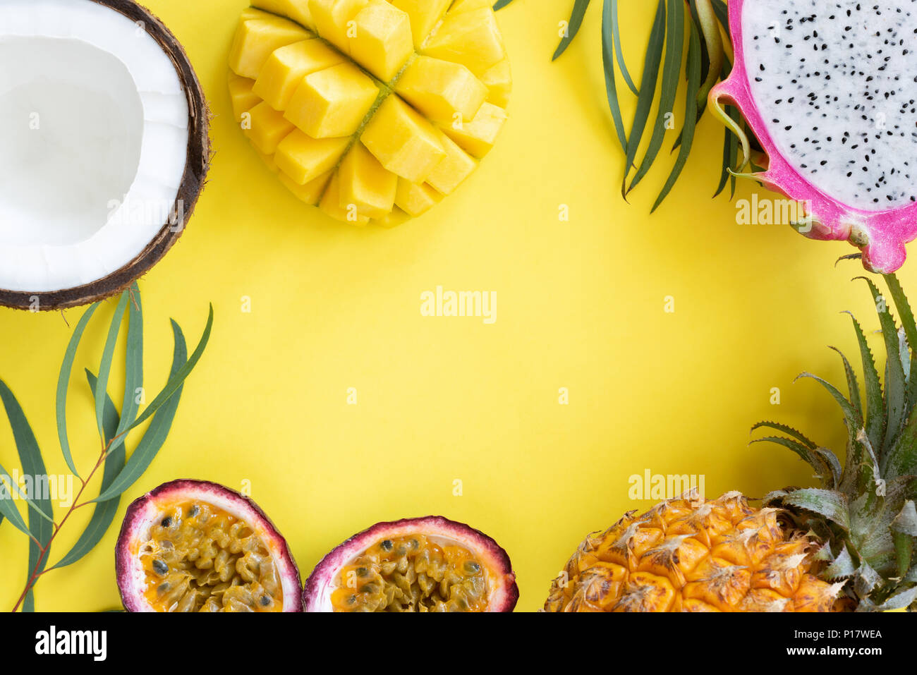 Tropical fruits mango, pitayam coconut and passion fruit on yellow background. Frame of resh fruits. Healthy lifestyle and summer concept - Stock Image