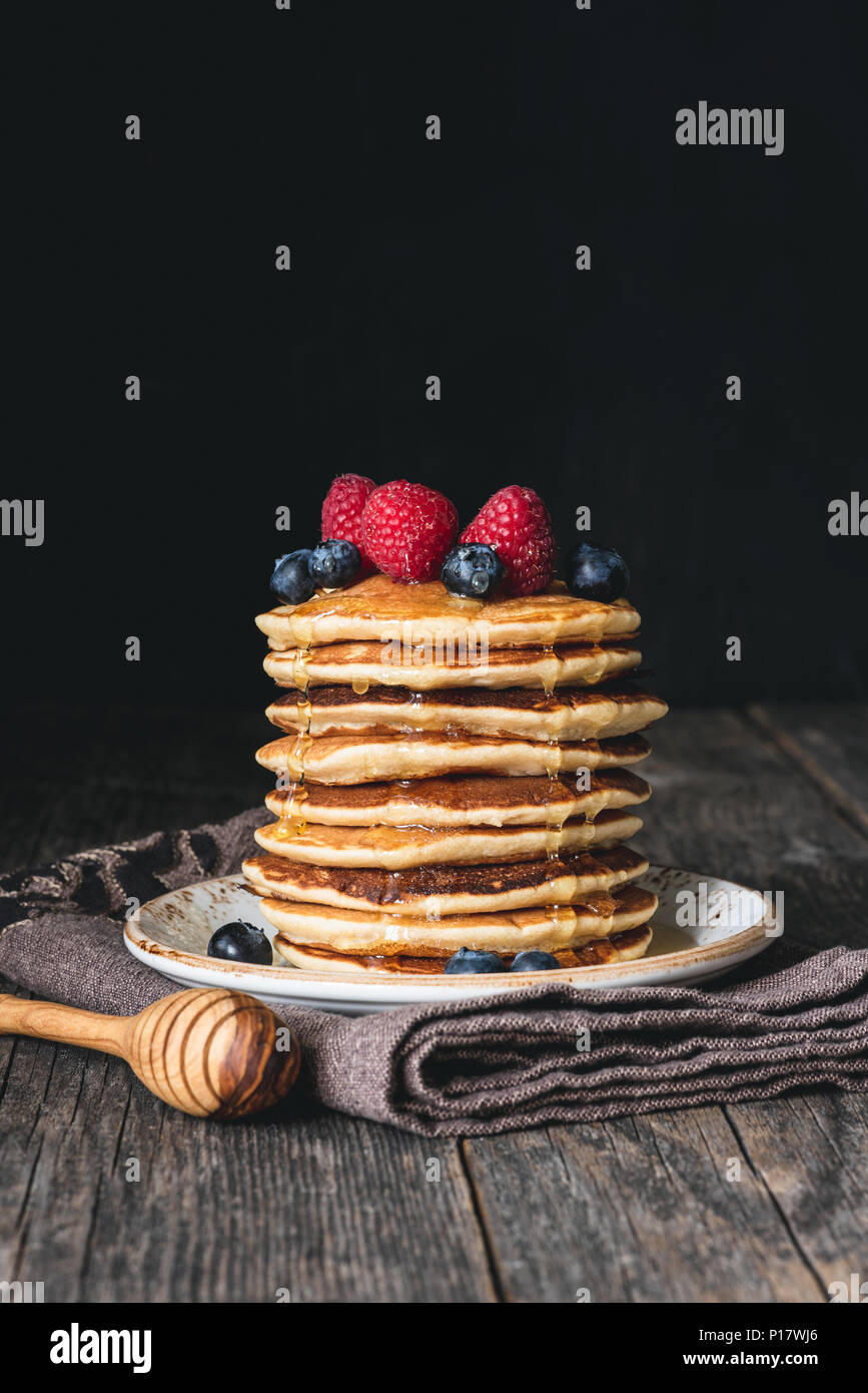 Stack of pancakes with honey and fresh berries on wooden table over dark background. Selective focus, copy space for text - Stock Image