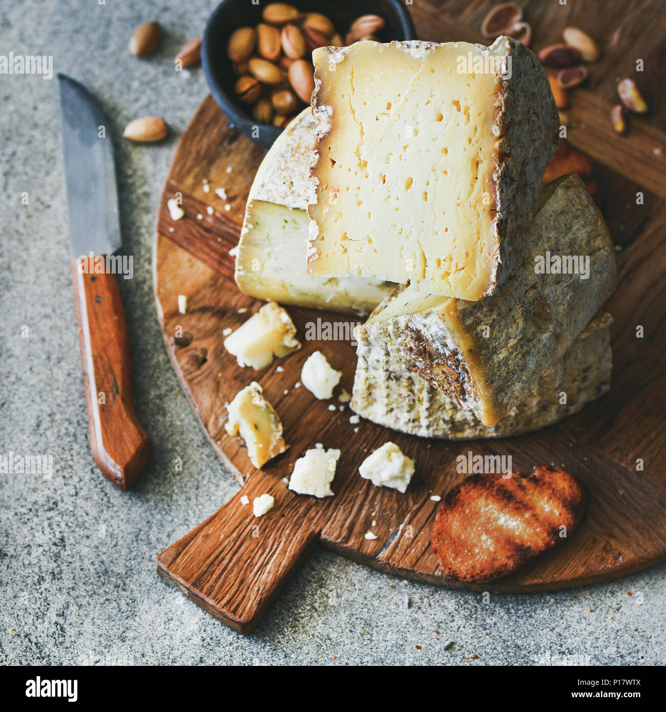Cheese platter with nuts, honey and bread, square crop - Stock Image