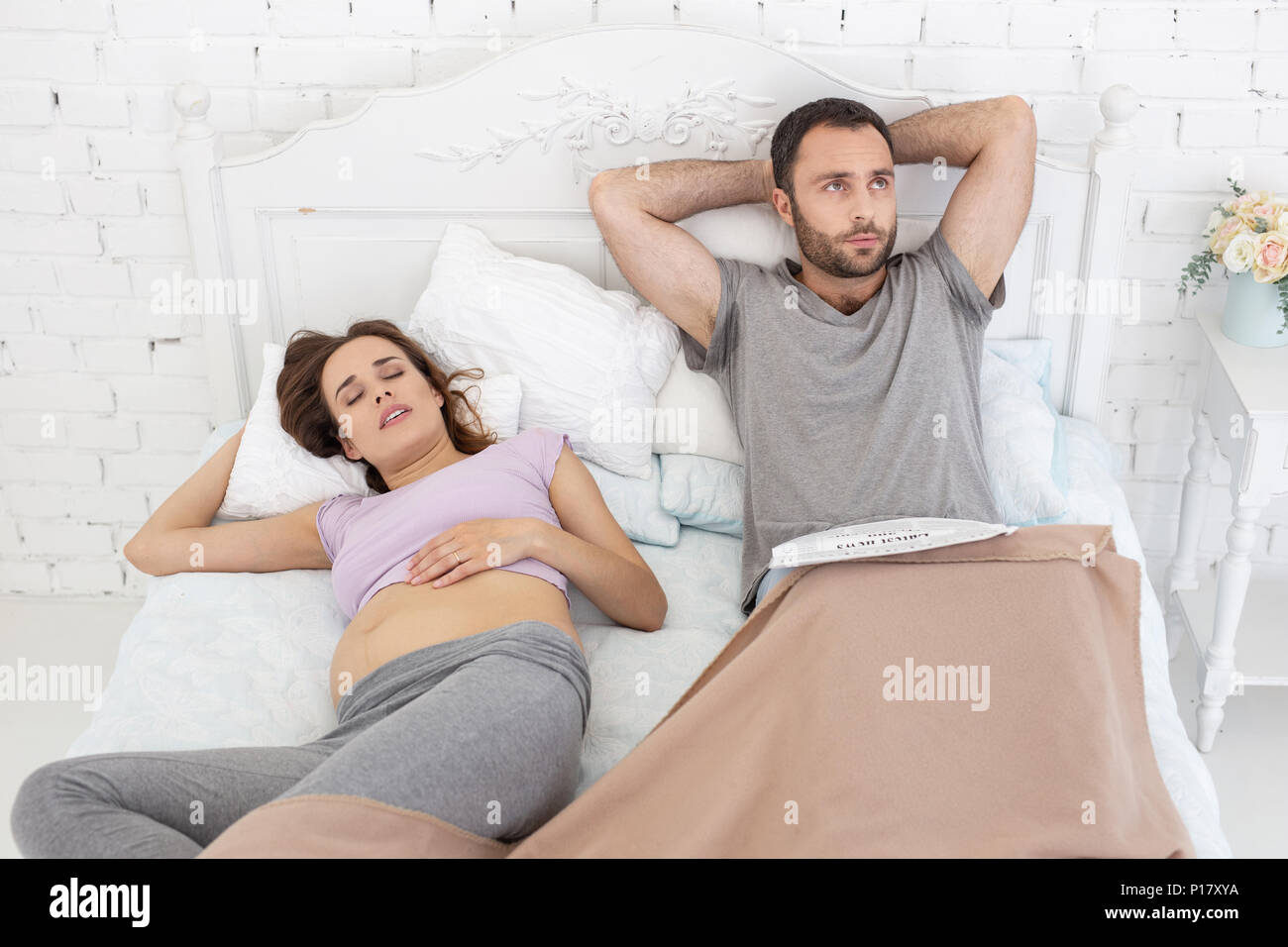 Attractive pregnant woman grunting while sleeping - Stock Image