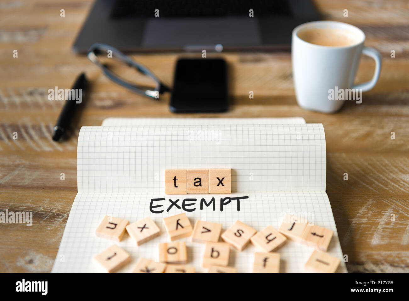 Closeup on notebook over vintage desk surface, front focus on wooden blocks with letters making Tax Exempt text. - Stock Image