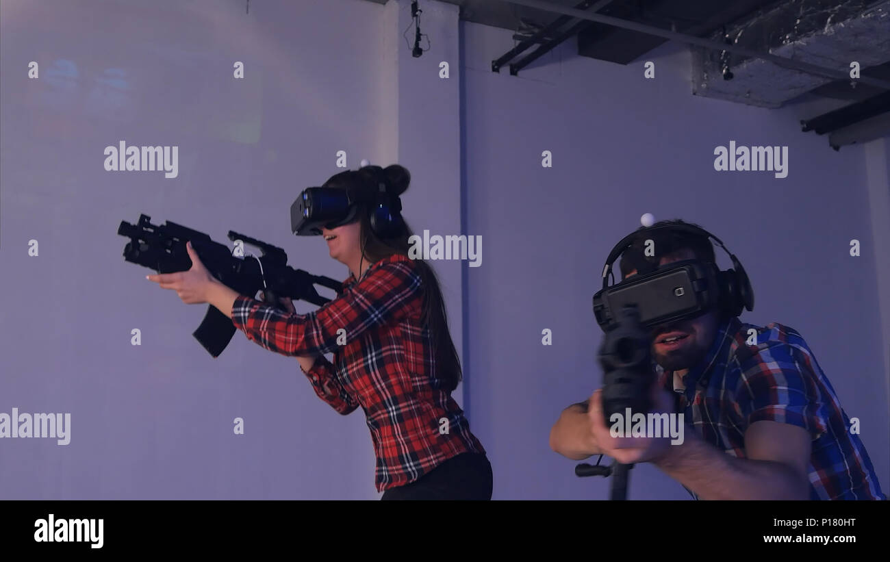 Young couple playing VR shooter game with virtual reality