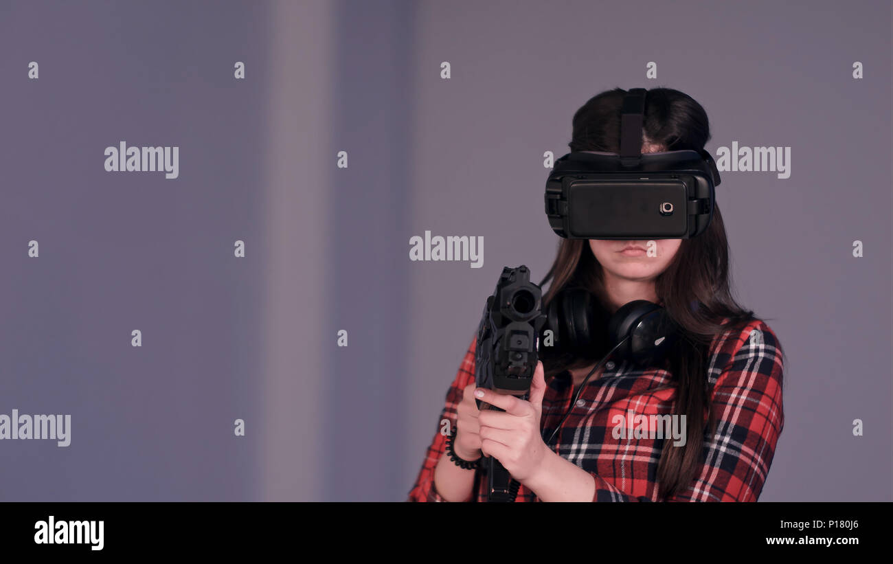 Girl wearing virtual reality glasses and holding a vr gun Stock