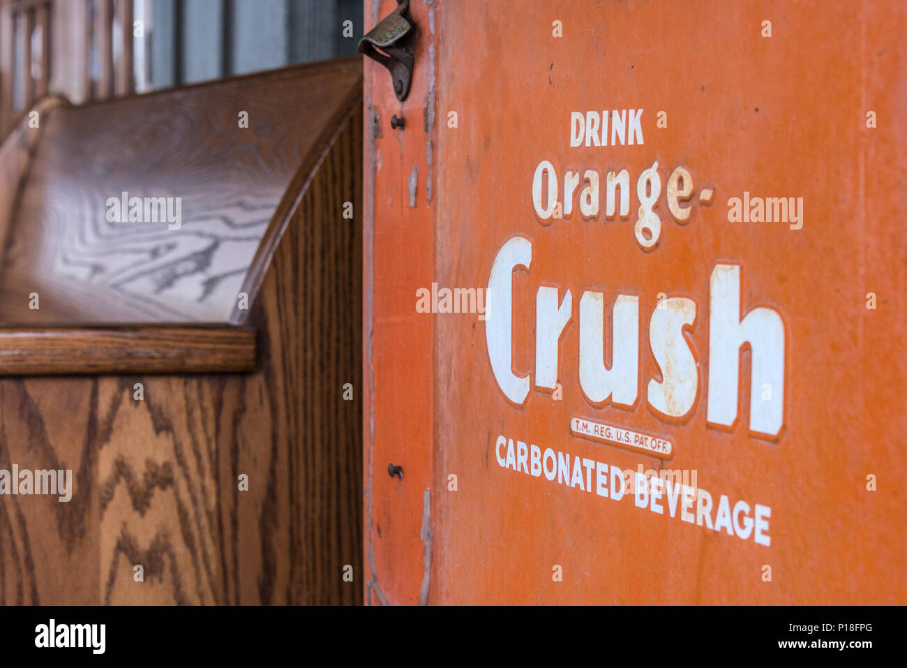 Vintage Orange Crush cooler with bottle opener next to an old church pew at Cracker Barrel Old Country Store in West Memphis, Arkansas. (USA) - Stock Image