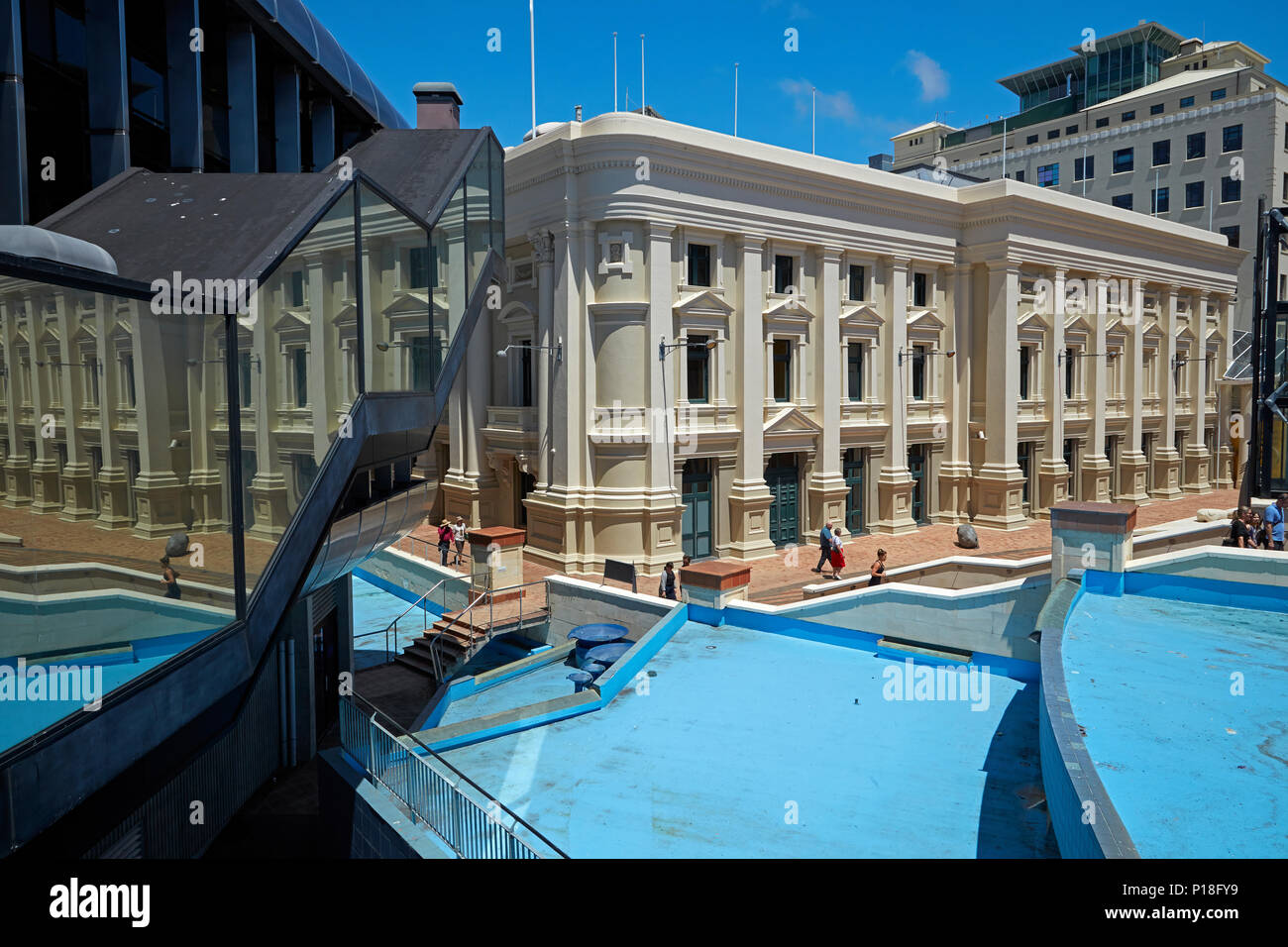 Wellington Town Hall, water feature, and reflection in Michael Fowler Centre, Civic Square, Wellington, North Island, New Zealand - Stock Image