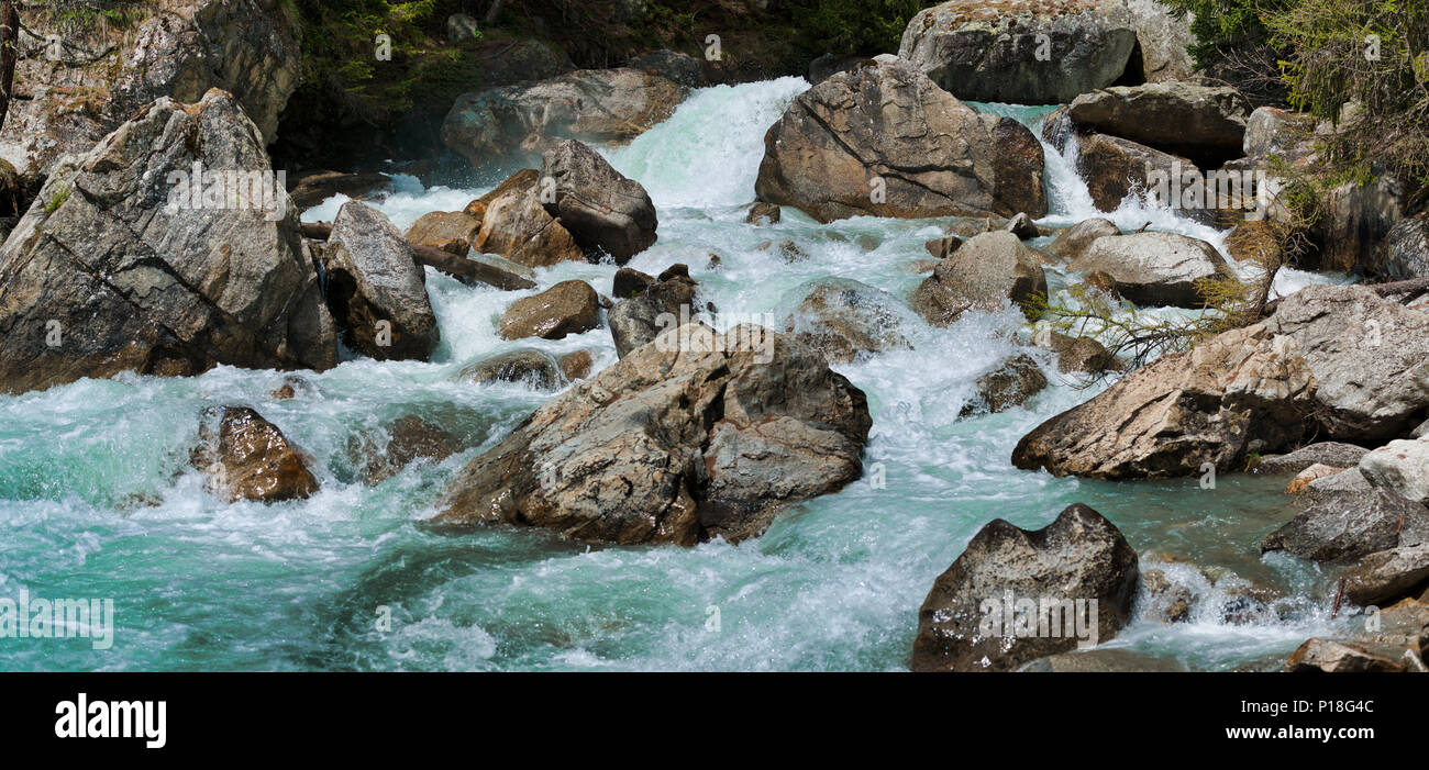 the rapids of the river that flows between the rocks during the melting snow - Stock Image