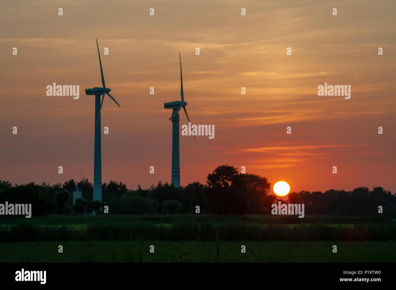 DE - Wind turbines in the sunset of Horumersiel - Stock Image
