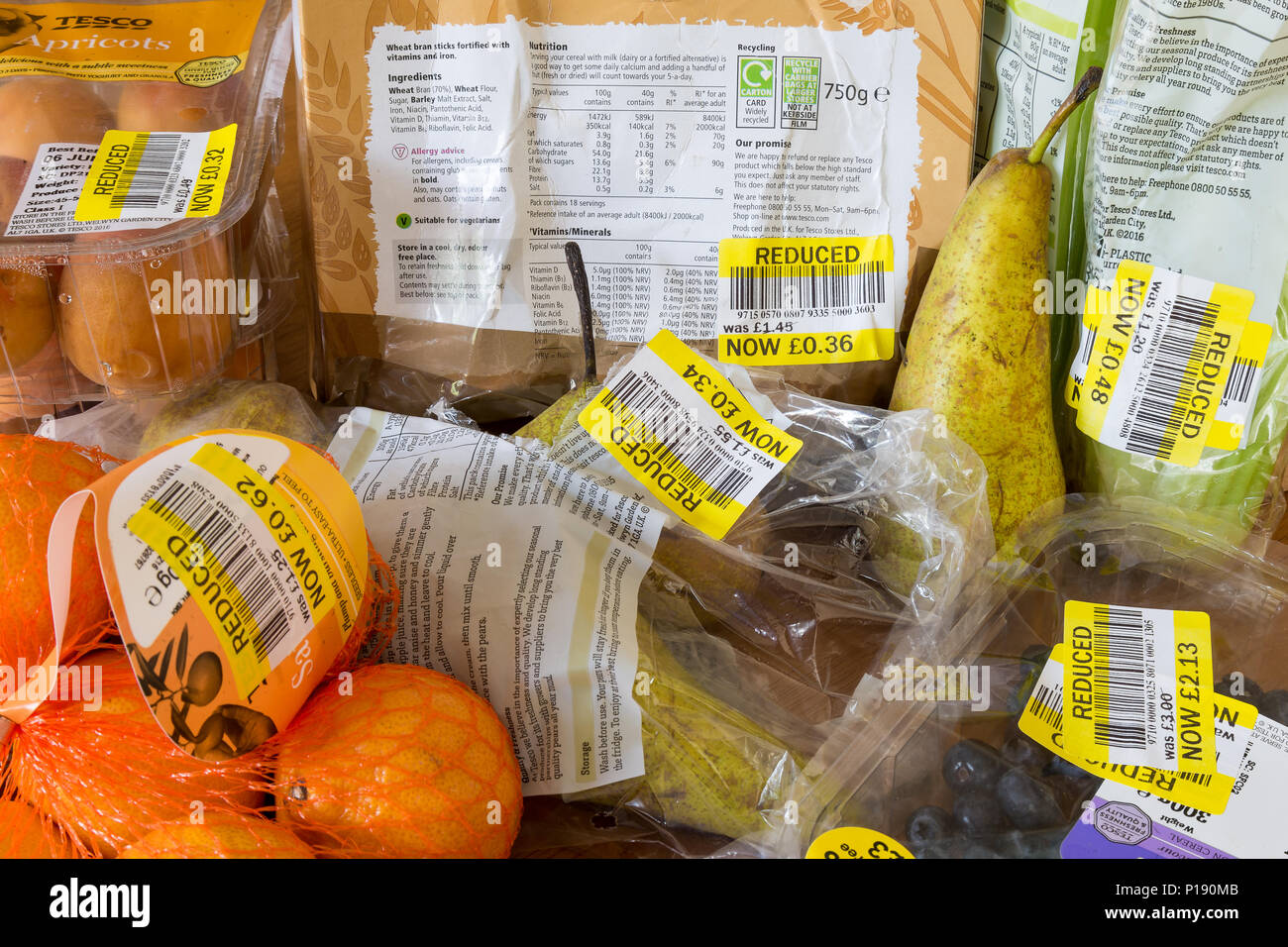 Thrifty shopping. Close up of food products purchased with yellow, reduced stickers. Fresh fruit past sell-by date, bought by family on tight  budget. - Stock Image