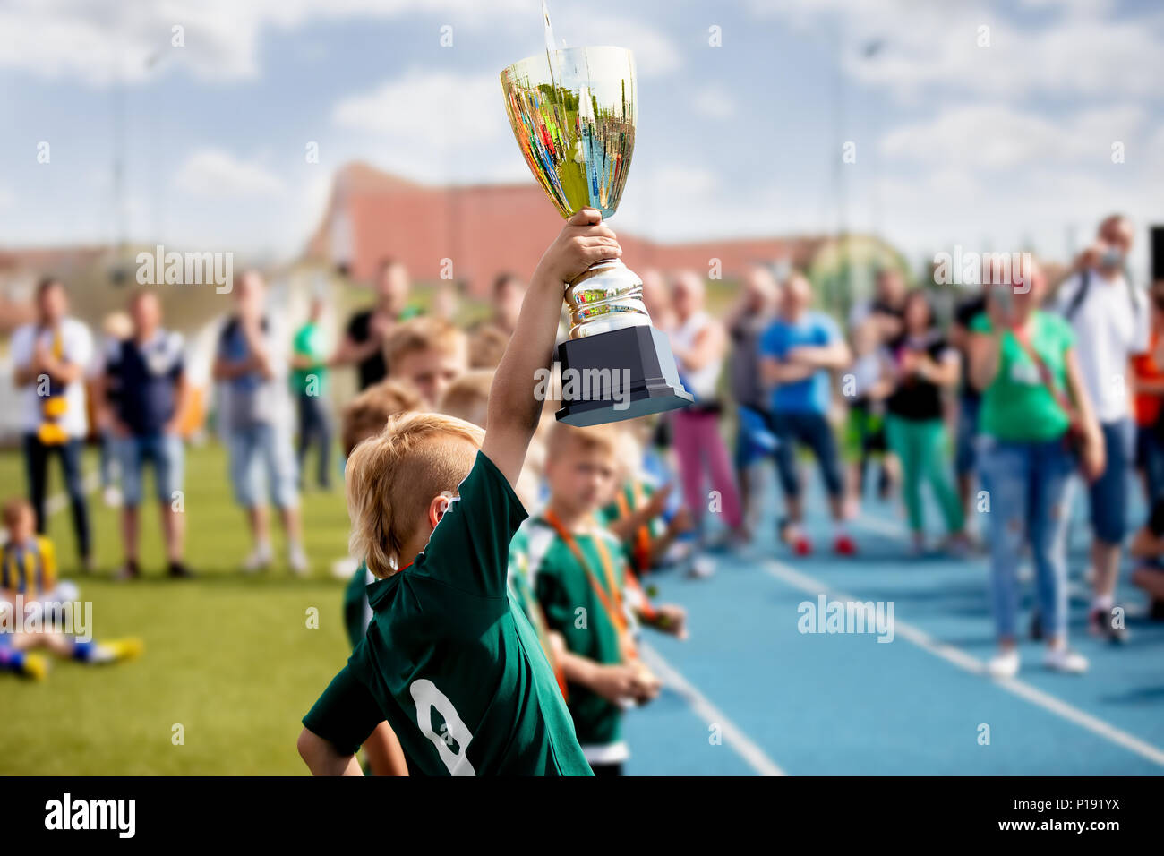 Young Boy Raising Golden Football Cup. Winning Youth Football Team Celebrating Success. Kids School Football Tournament Handing Out Prizes Stock Photo