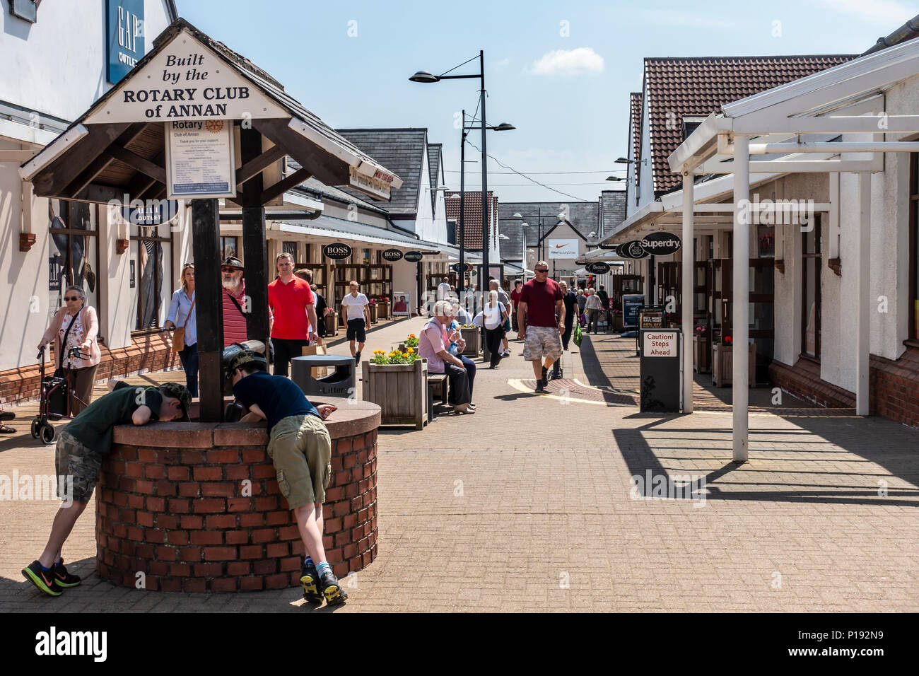Shoppers enjoying a sunny day browsing the shops of Gretna Gateway Outlet Village, a 'strip mall' in the very south of Scotland. - Stock Image