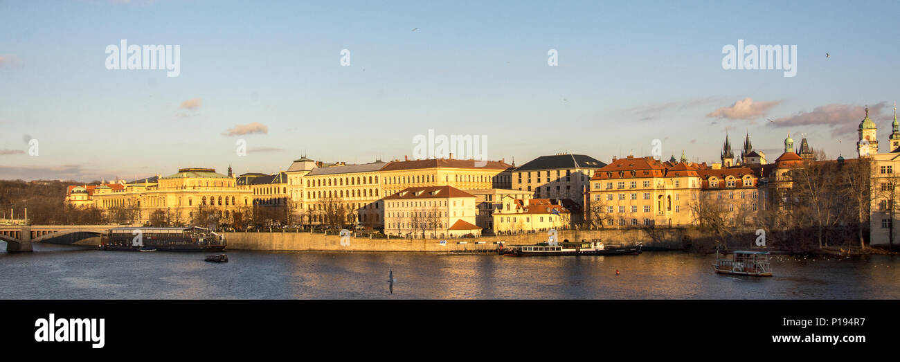 Beautiful view on the historic centre of Prague, capital of the Czech Republic, with river Moldau, in golden sunlight at the end of a winter's day - Stock Image