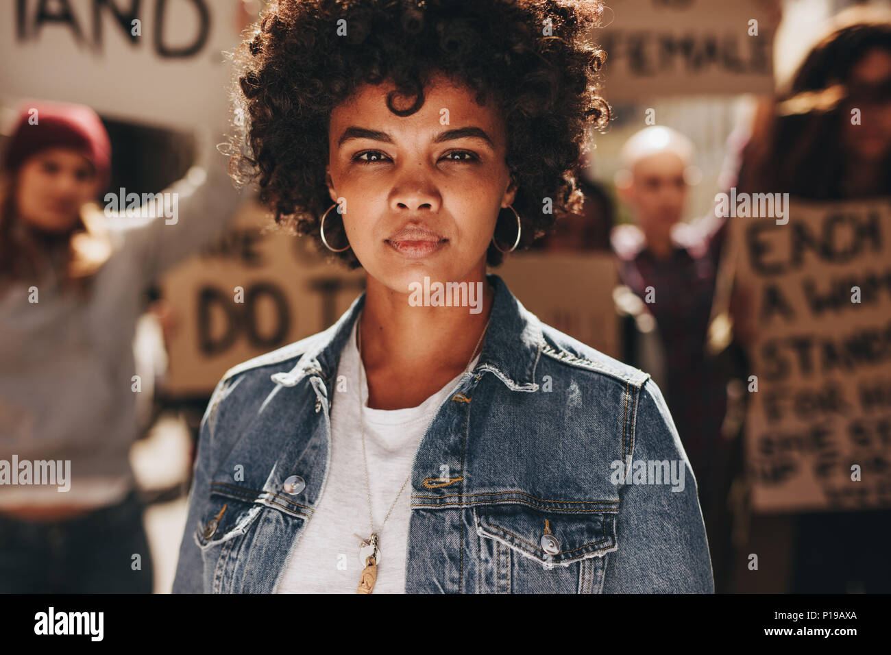 Young african woman standing outdoors with group of demonstrator in background. Woman protesting with group of activists outdoors on road. - Stock Image