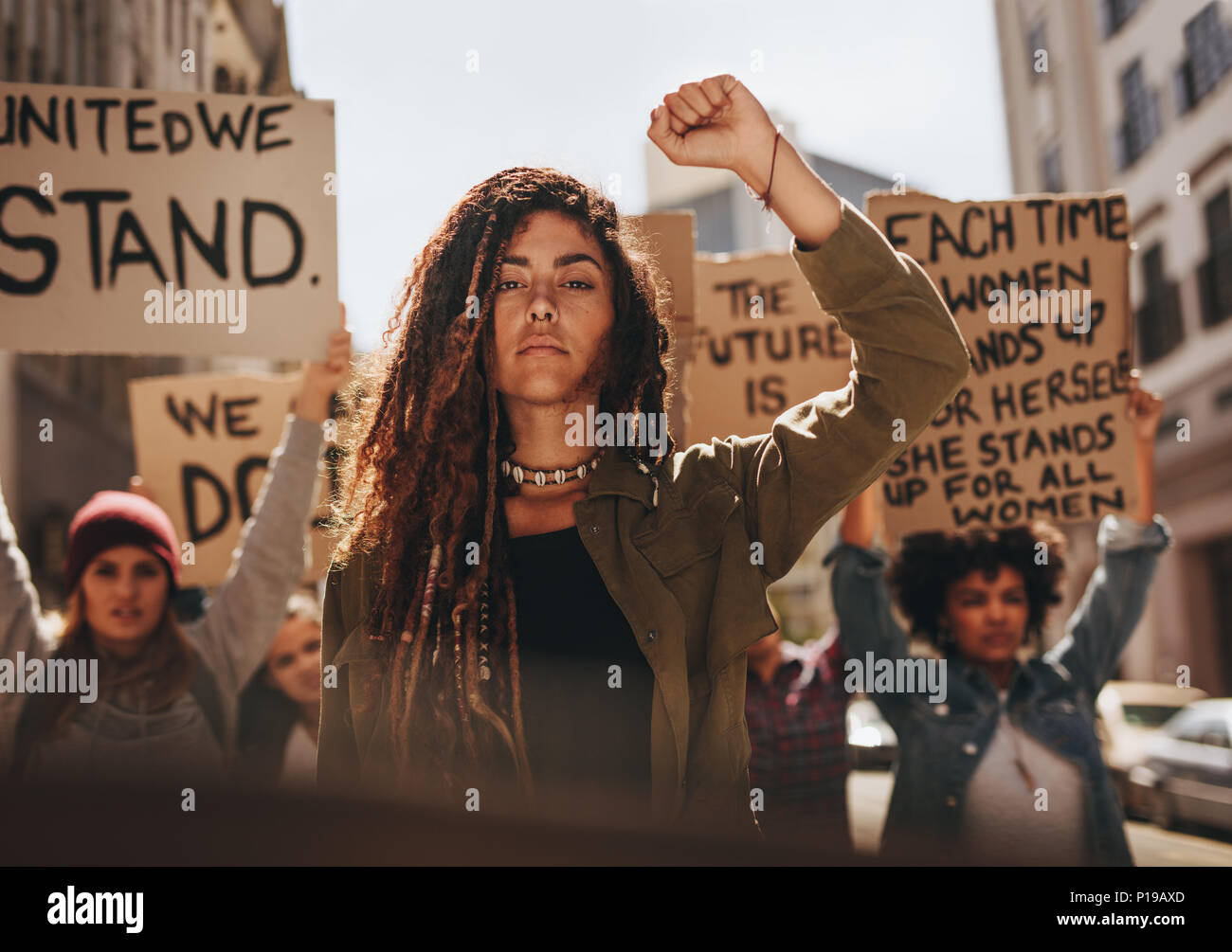 Woman leading a group of demonstrators on road. Group of female protesting for equality and women empowerment. - Stock Image