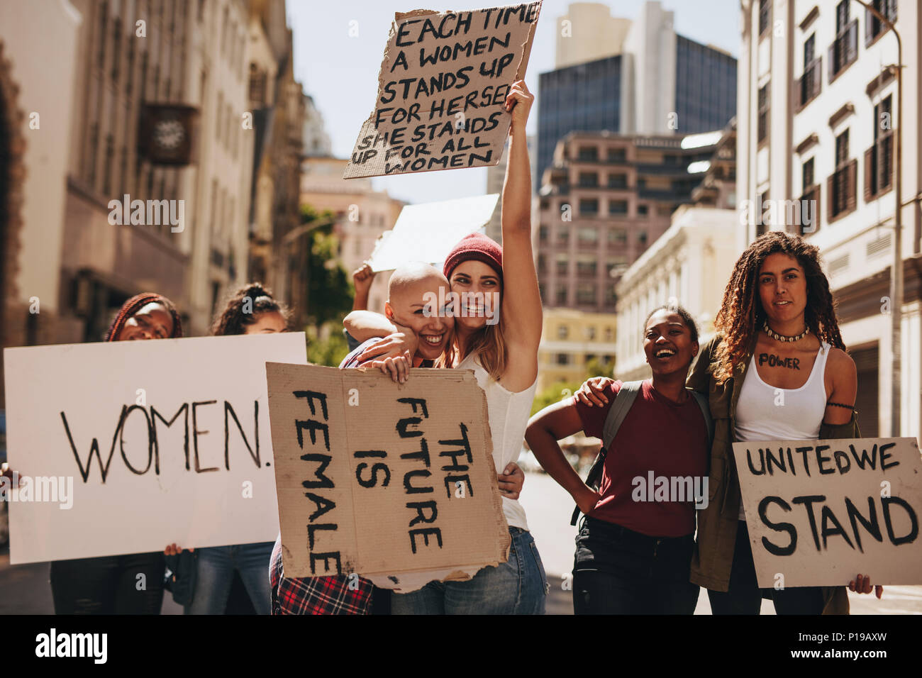 Crowd of protesters hold signs and rally on road. Group of women protesting for women empowerment and equality. - Stock Image