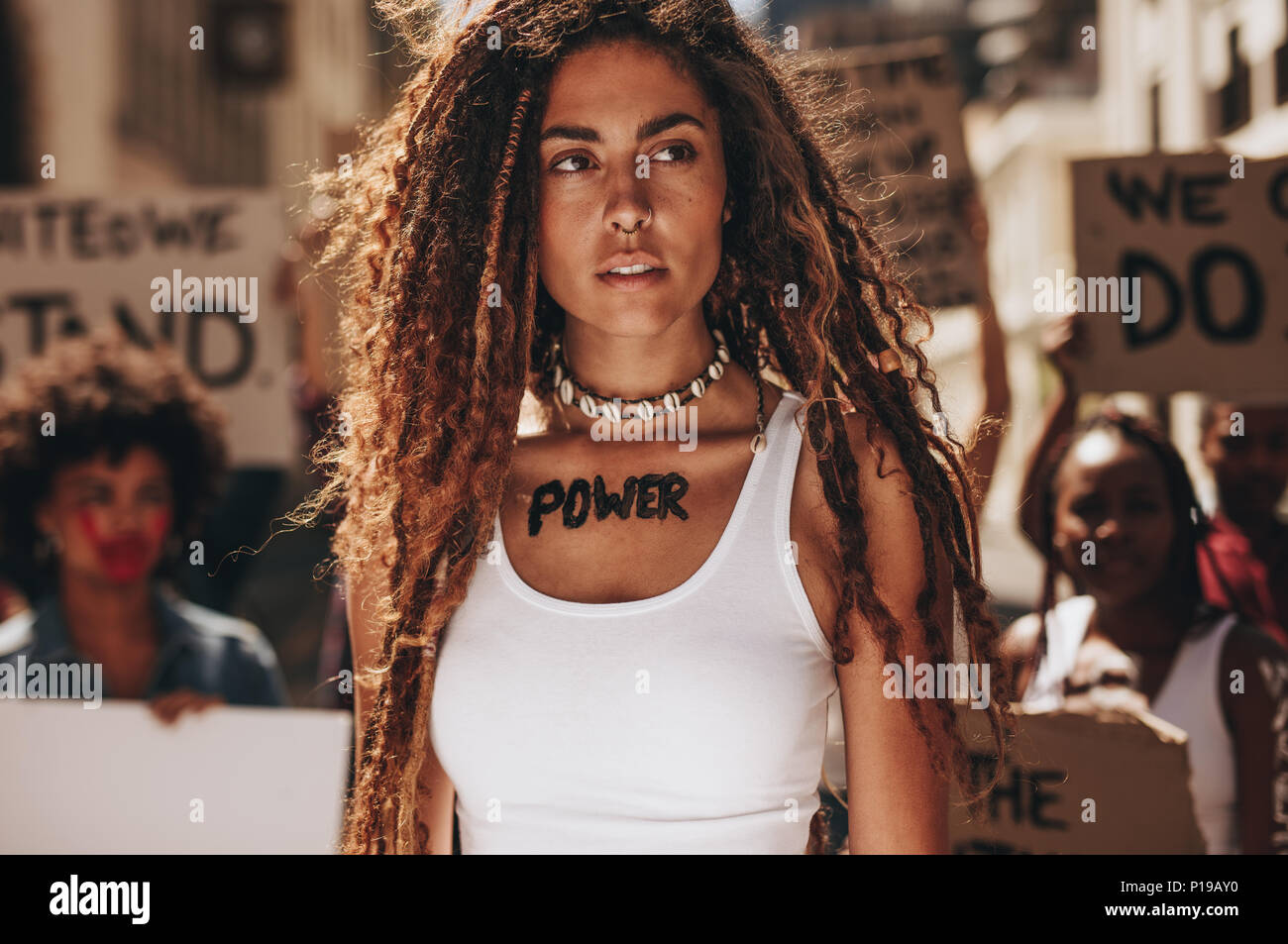 Young woman standing outdoors with group of activists in background. Woman with word power written on her chest and looking away. - Stock Image