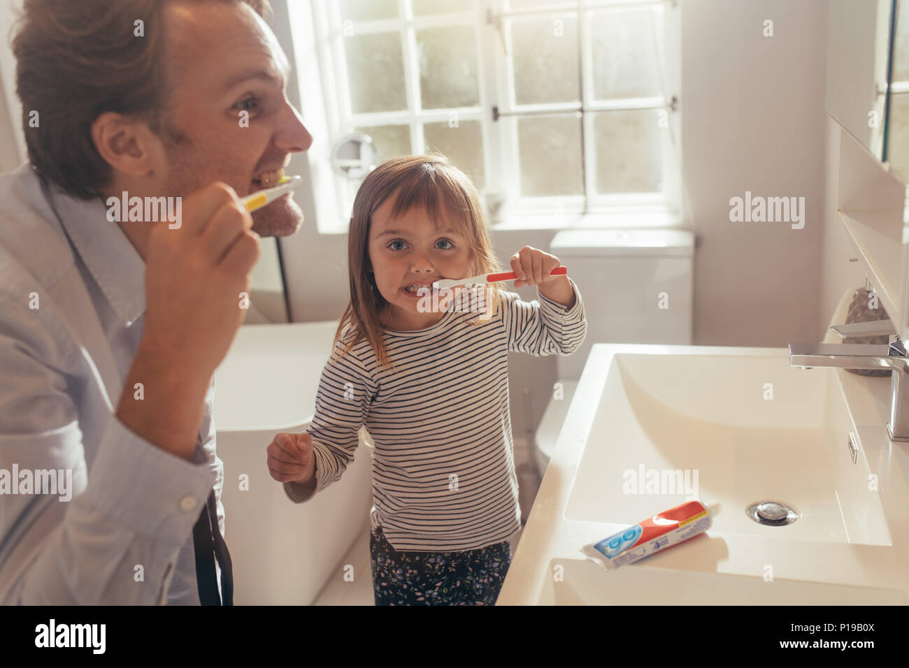 Father and daughter brushing teeth standing in bathroom. Man teaching his daughter how to brush teeth. - Stock Image