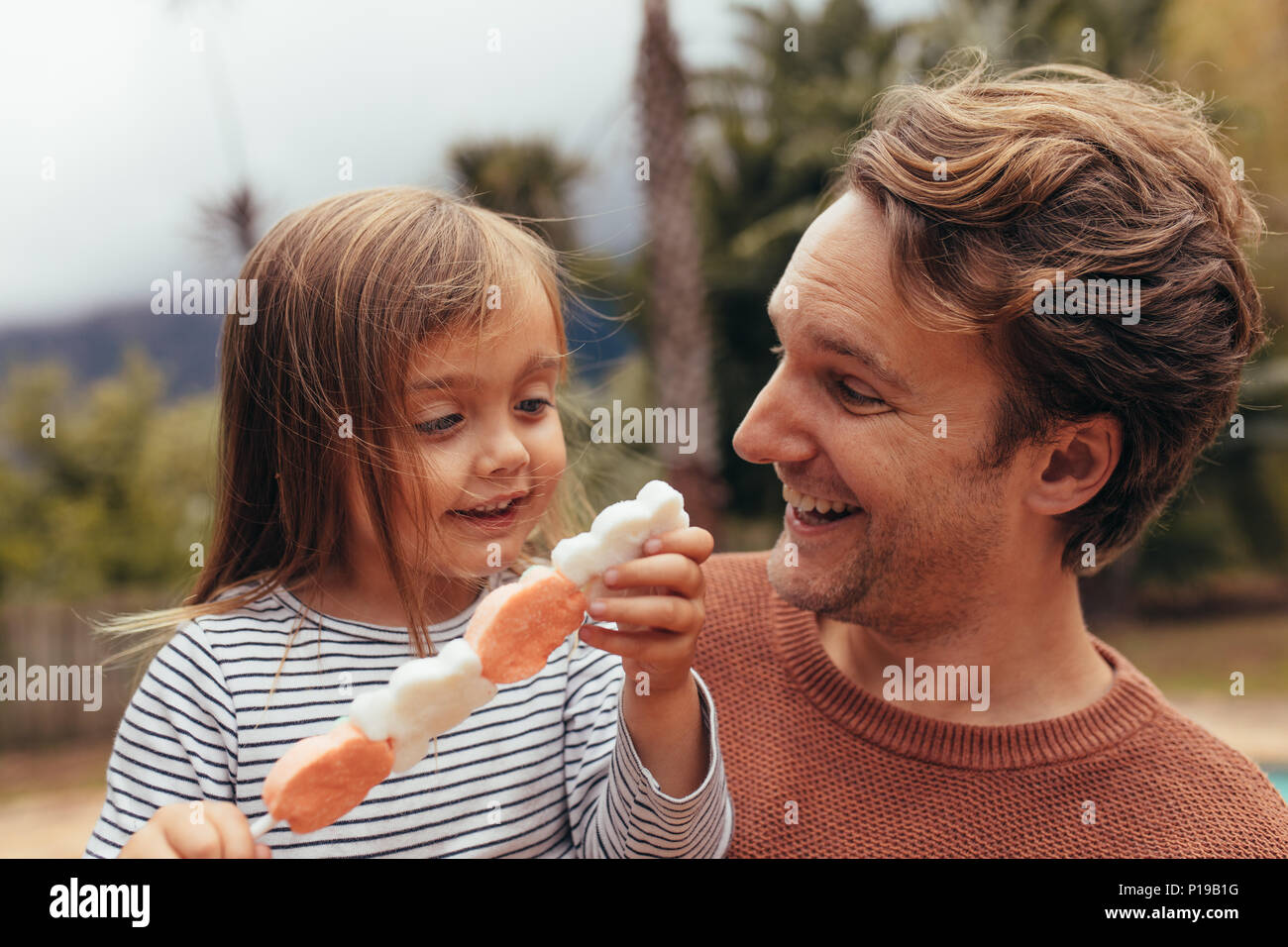 Happy daughter with her father holding a sugar candy stick outdoors. Father and daughter spending time together eating sugar candy. - Stock Image