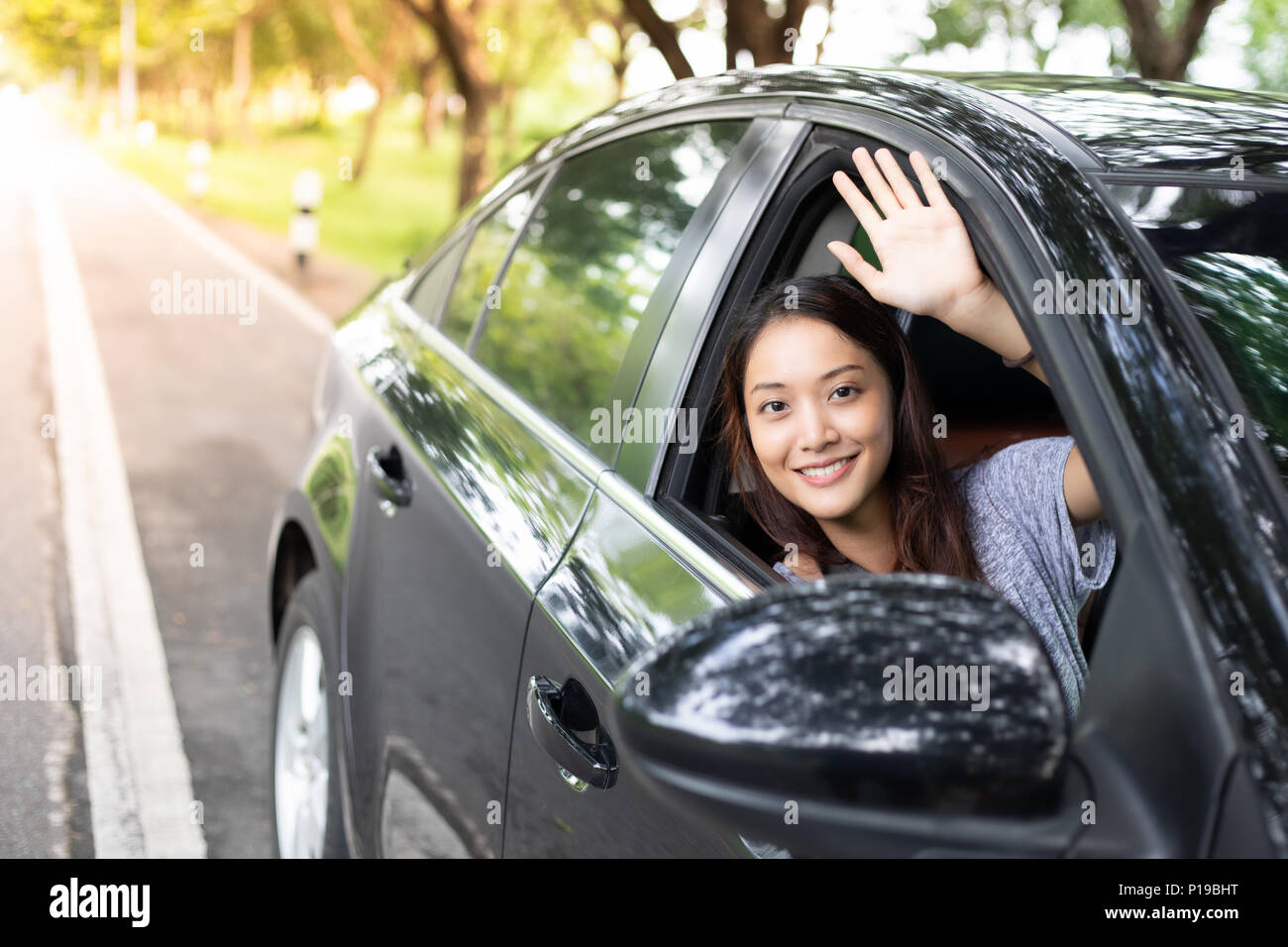 Beautiful Asian woman smiling and enjoying.driving a car on road for travel - Stock Image