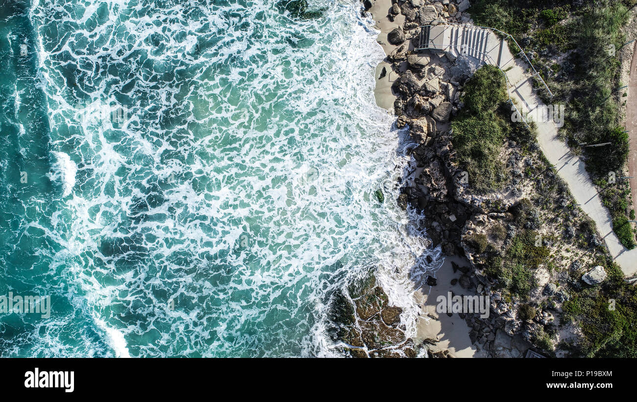 Aerial view ocean surf sea water washing onto sandy shoreline with stairs leading to beach - Stock Image