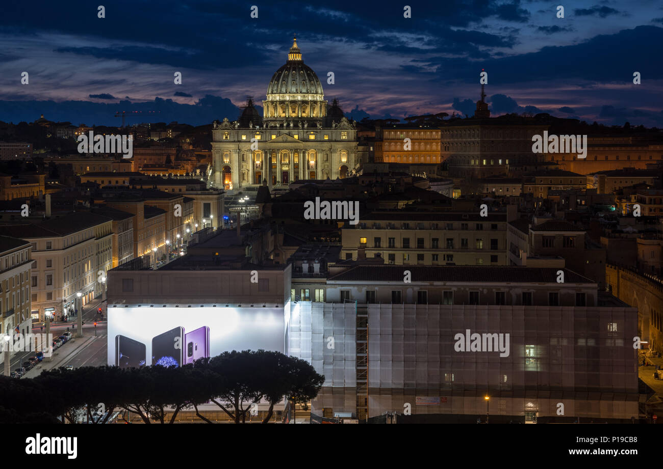 Rome, Italy - March 24, 2018: St Peter's Basilica and the Vatican City are lit up at sunset. - Stock Image