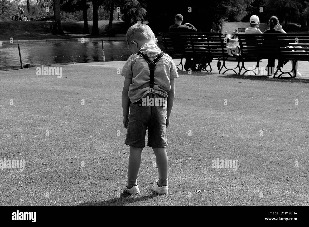 sad young boy standing alone in shorts black and white photo - Stock Image