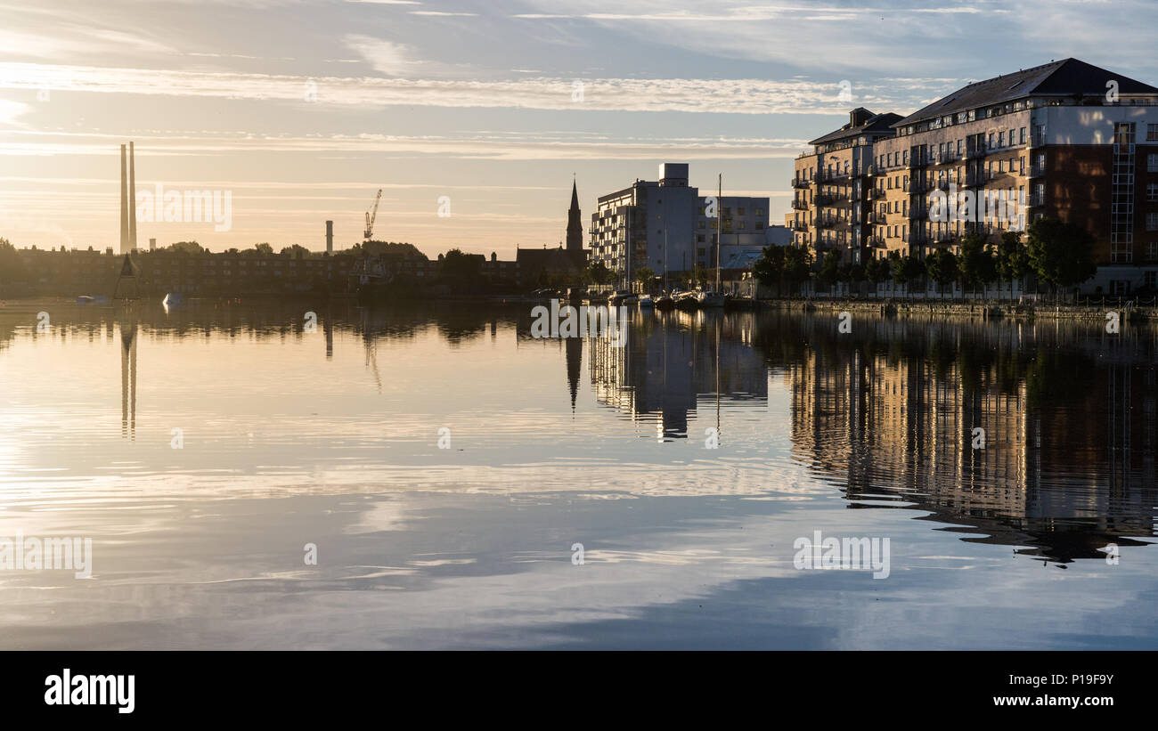 Dublin, Ireland - September 18, 2016: The landmark twin chimneys of Poolbeg Power Station and modern office and appartment buildings are reflected in  - Stock Image