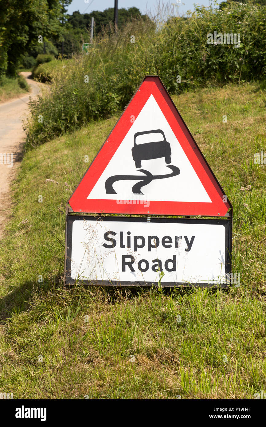 Red triangle road sign warning of Slippery Road, Suffolk, England, Uk - Stock Image