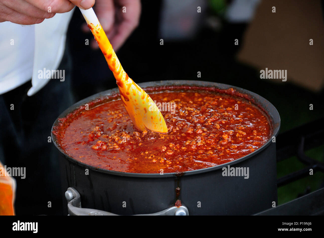 Cook Stirring a Simmering Pot of Spicy Chili - Stock Image