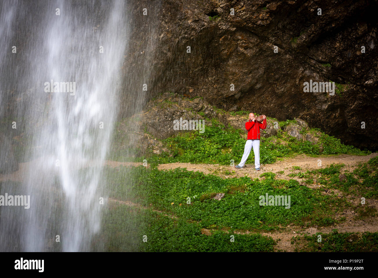 Man in casual wear blows the conch shell behind giant watefall - Stock Image