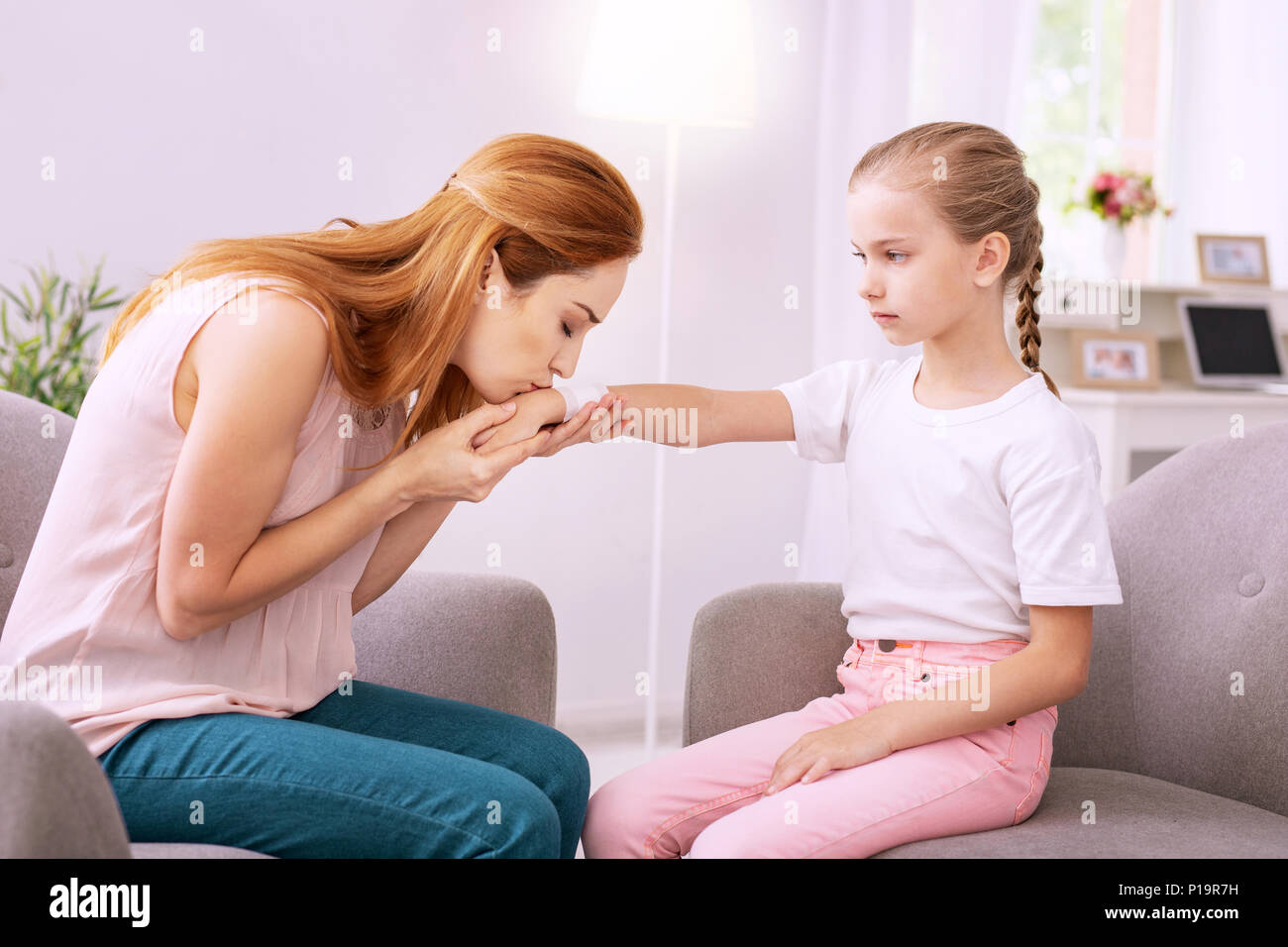 Pleasant anxious woman kissing her daughters hand Stock Photo