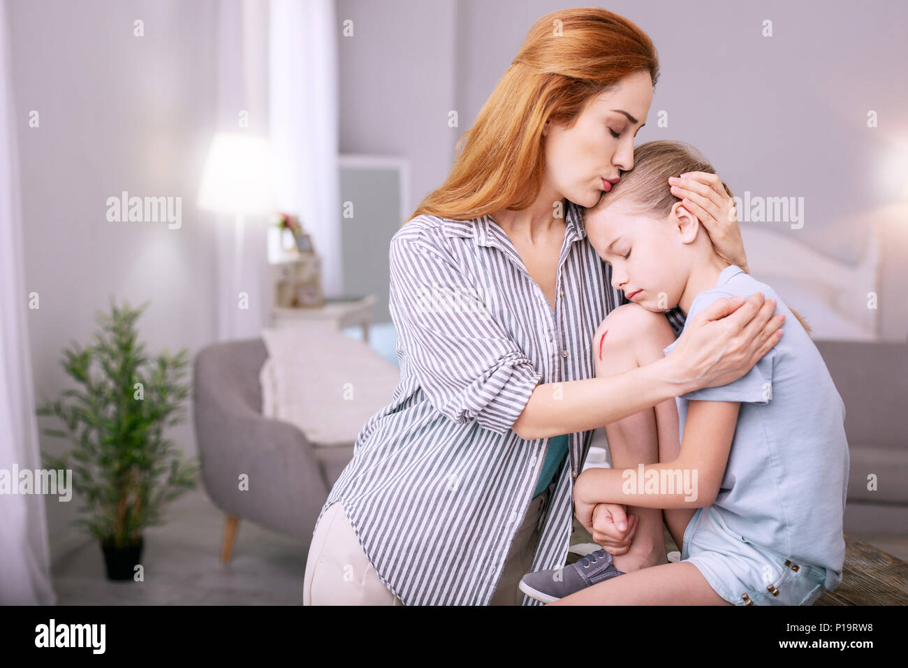 Pleasant loving mother kissing her child - Stock Image