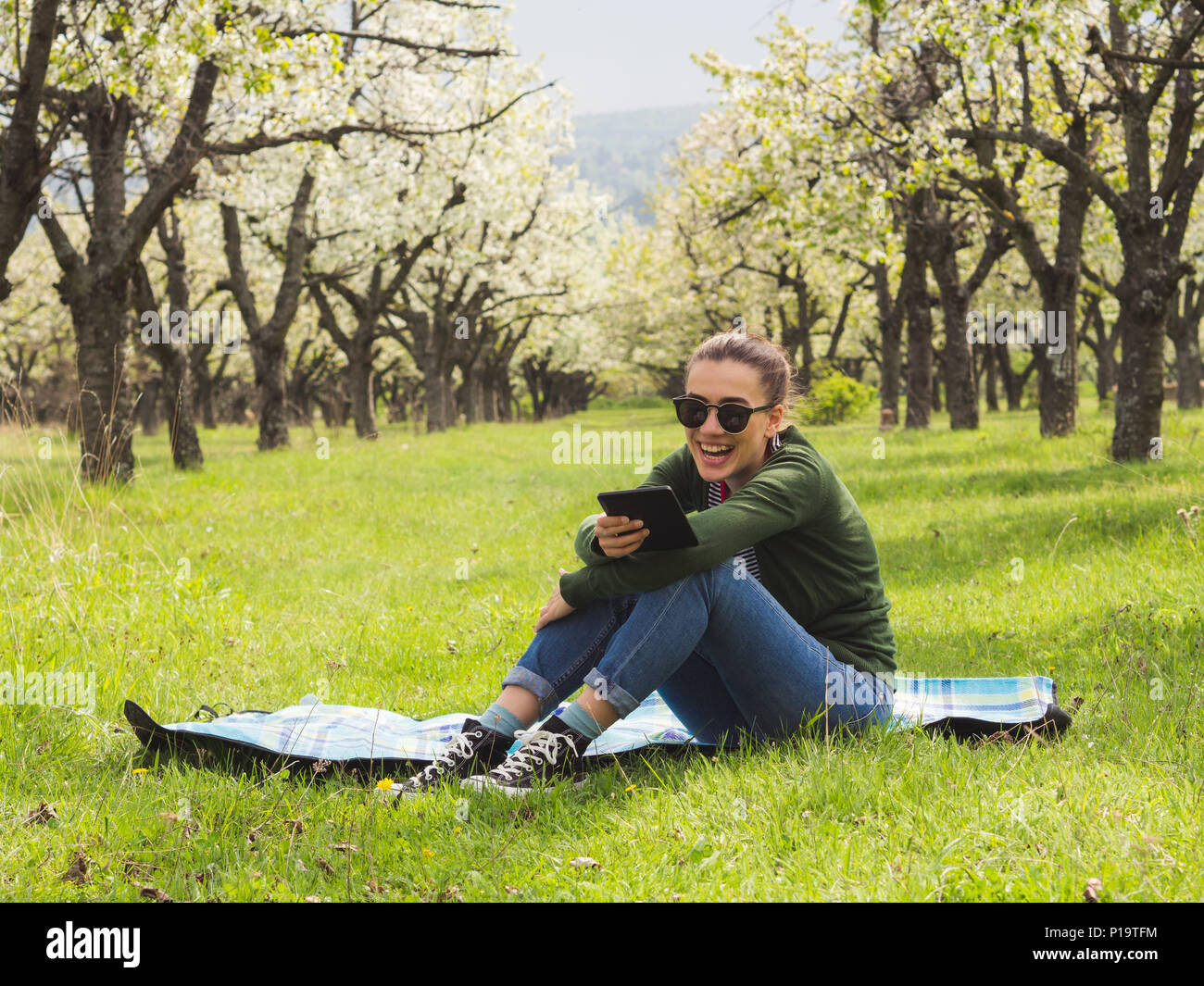 Young attractive woman reading on her ebook outdoors and laughing - Stock Image