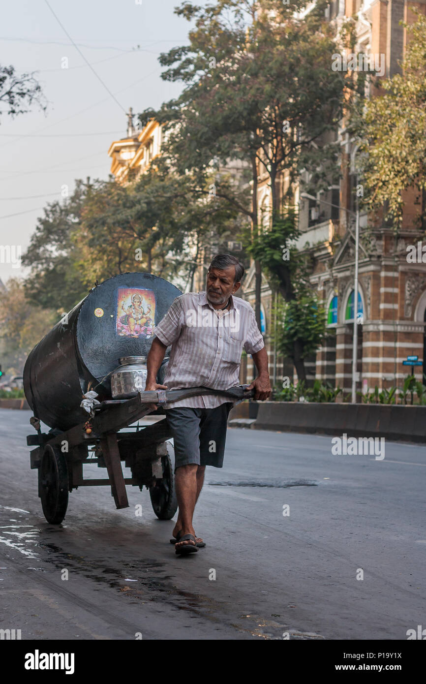 MUMBAI, INDIA - DECEMBER 4,2016 : Old age worker pulling goods cart in the middle of Mumbai street - Stock Image