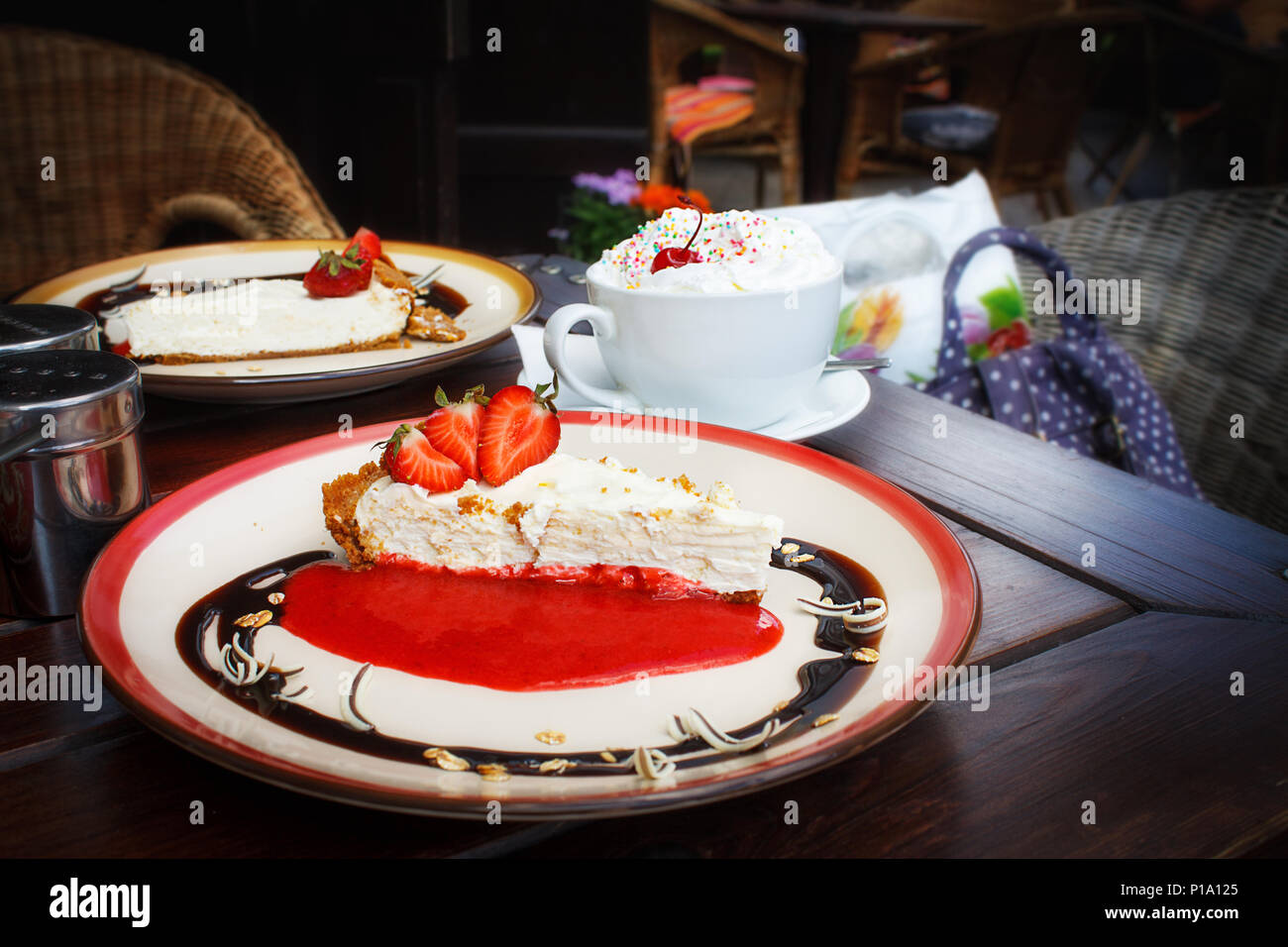 Cheesecake with fresh strawberries on plate and a cup of Viennese coffee with whipped cream on a brown wooden table in a summer outdoor cafe. Relaxing cozy old town atmosphere. offee break, dessert. - Stock Image