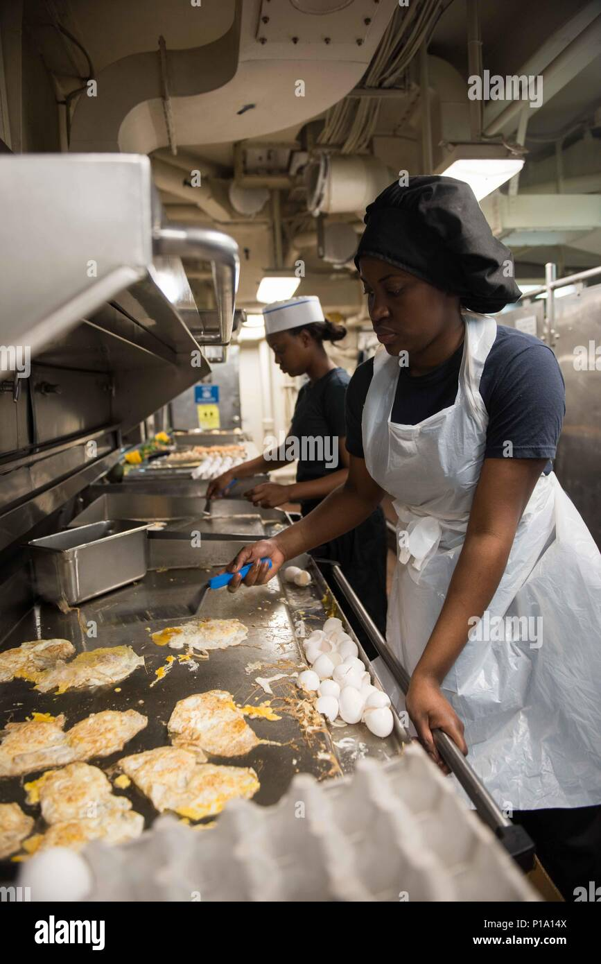 161002-N-BR087-096  PACIFIC OCEAN (Oct. 2, 2016) Petty Officer 2nd Class Selima Rougier, from Brooklyn, New York, fries eggs for brunch in USS John C. Stennis' (CVN 74) aft galley. John C. Stennis is underway conducting proficiency and sustainment training. (U.S. Navy photo by Seaman Cole C. Pielop / Released) Stock Photo