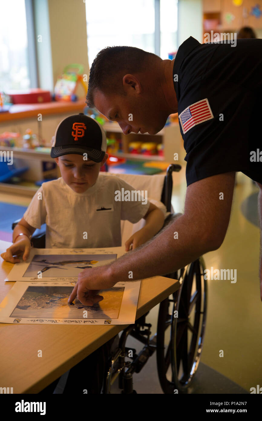 U.S. Navy Petty Officer 1st Class Brian Coffman, the leading petty officer of avionics with the Blue Angels presents Blue Angels memorabilia to a patient at the University of California San Francisco Benioff Children's Hospital, San Francisco, Oct. 4, 2016. The Blue Angels, along with Marines from I Marine Expeditionary Force visited the children at the hospital. Marines and Sailors with I MEF and Third Fleet arrived on USS San Diego (LPD 22)  to participate in San Francisco Fleet Week 2016 to demonstrate the Marine Corps' ability to integrate with the Navy to provide the world's premier crisi - Stock Image