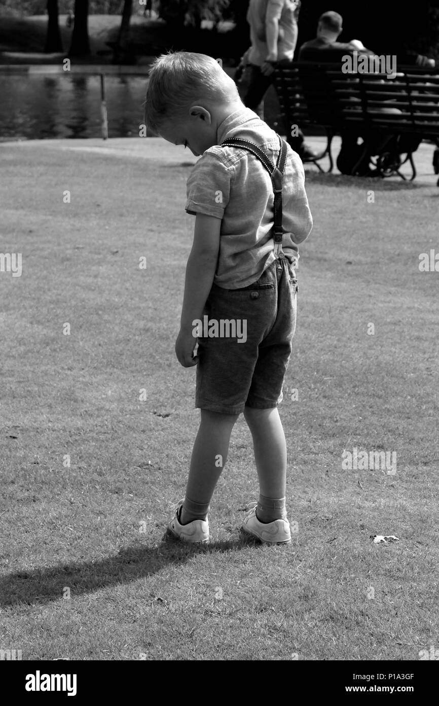 young boy standing alone in shorts black and white photo - Stock Image